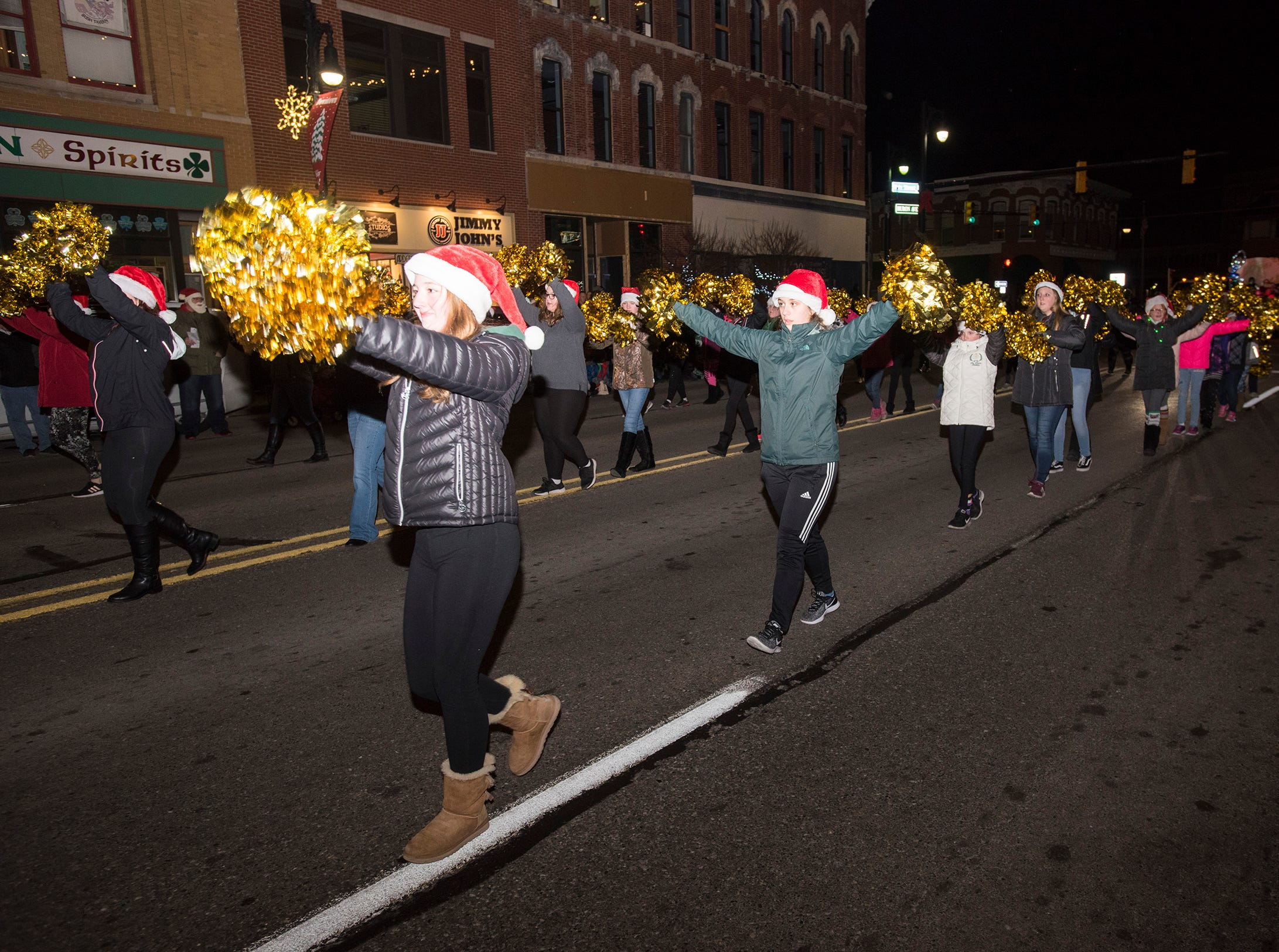 Participants walk in Sperry's Santa Claus Parade Friday, Nov. 23, 2018 in downtown Port Huron.