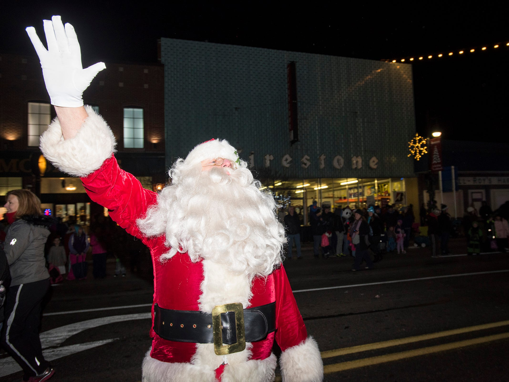 Santa Claus waves to spectators as he walks in Sperry's Santa Claus Parade Friday, Nov. 23, 2018 in downtown Port Huron.