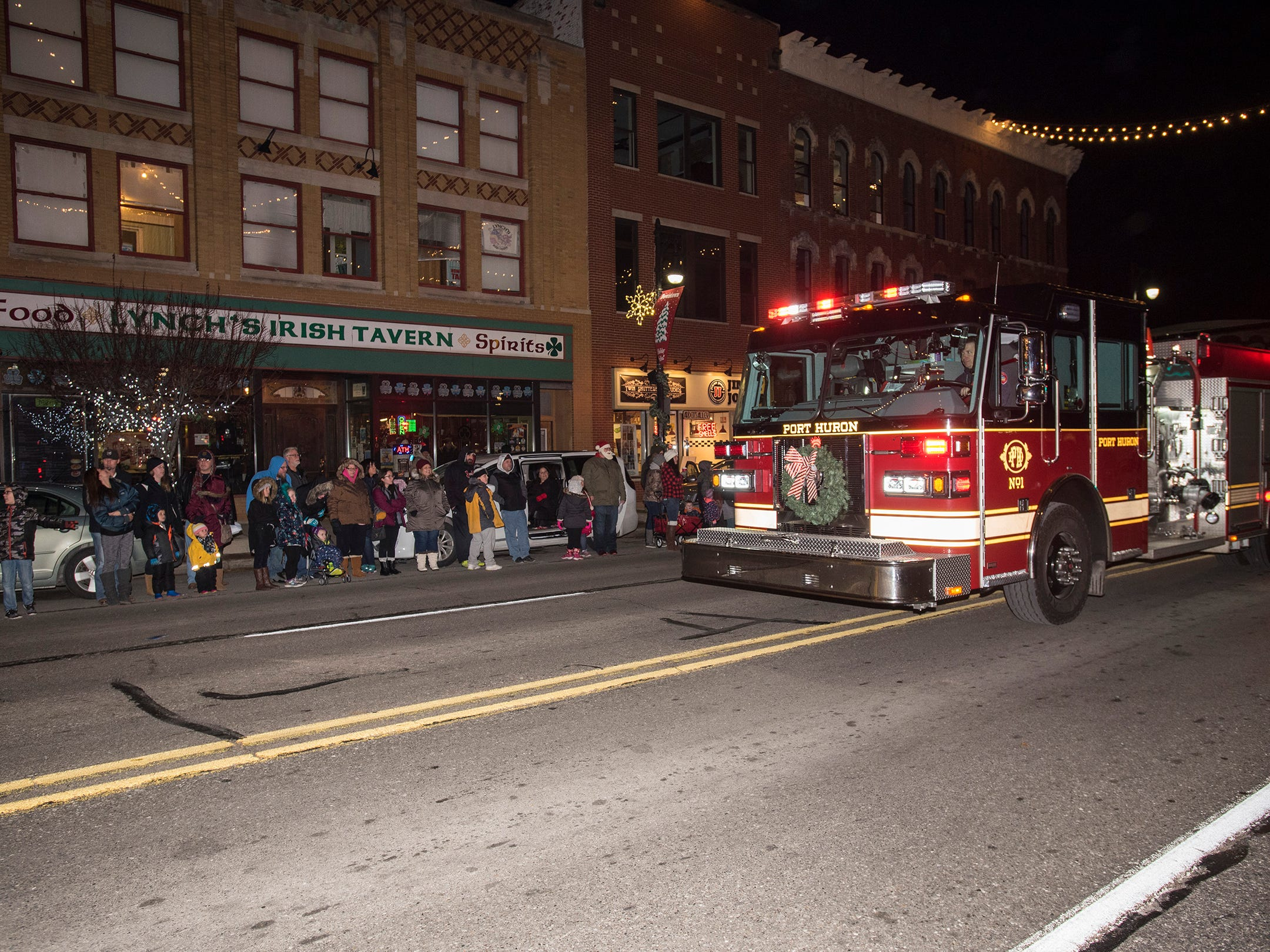 A Port Huron firetruck drives down Huron Avenue during Sperry's Santa Parade Friday, Nov. 23, 2018 in Port Huron.