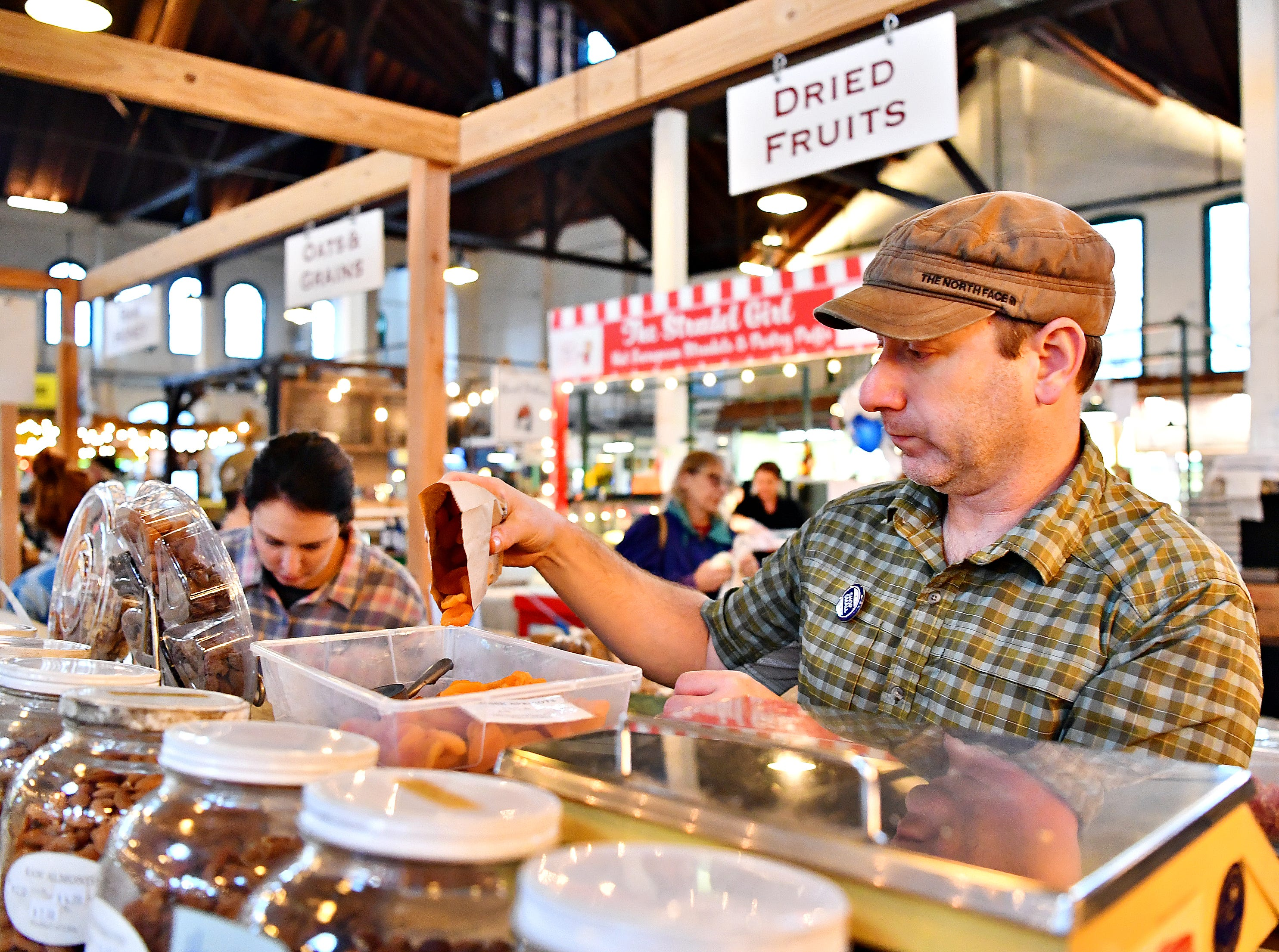 Owner Kevin Westover, of ComplEAT, prepares to weigh Turkish apricots to fill an order during Small Business Saturday at Central Market in York City, Saturday, Nov. 24, 2018. Dawn J. Sagert photo