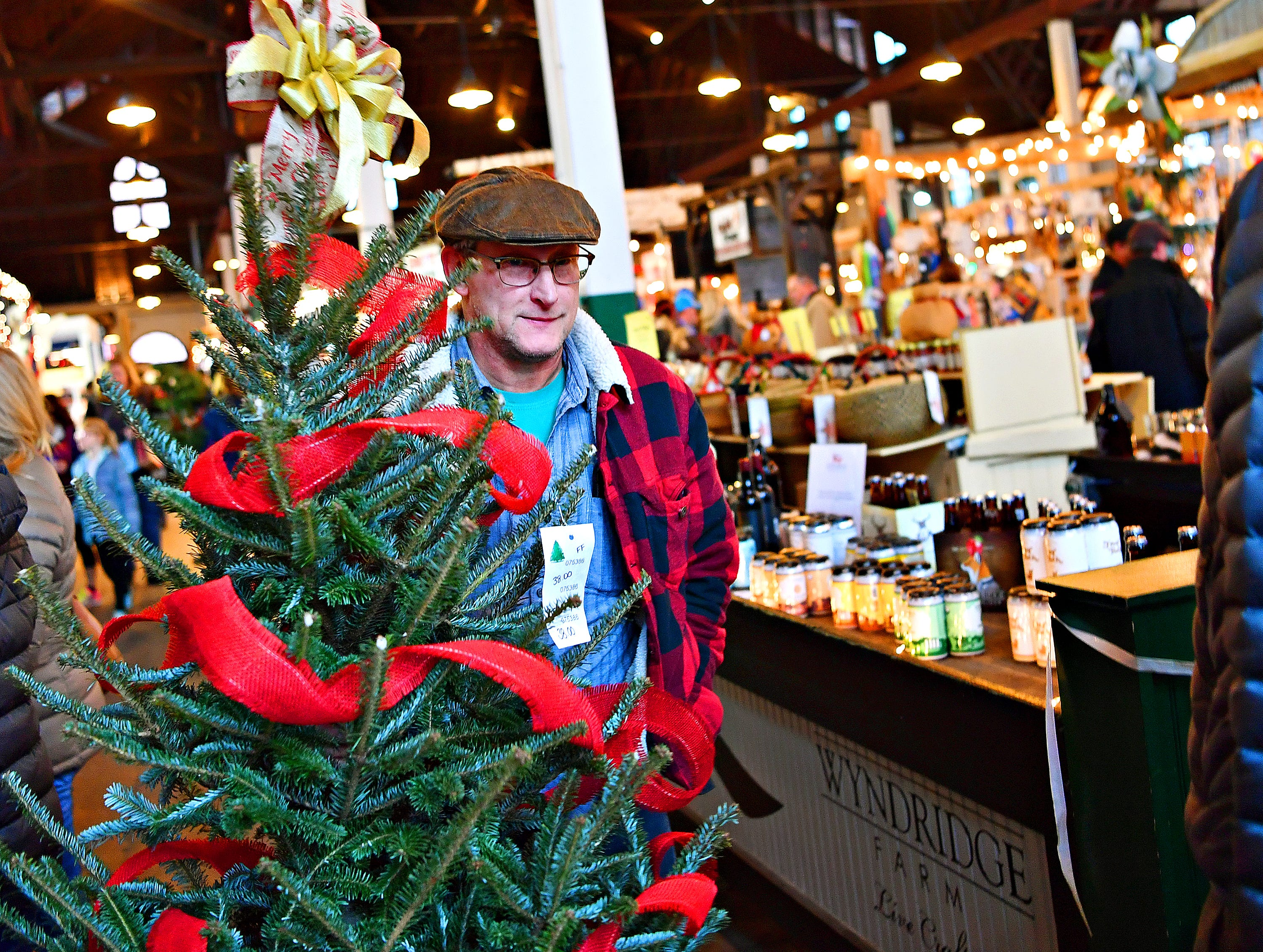 Todd Sauter, of West Manchester Township, carries his freshly cut Christmas Tree out of Central Market during Small Business Saturday in York City, Saturday, Nov. 24, 2018. Dawn J. Sagert photo
