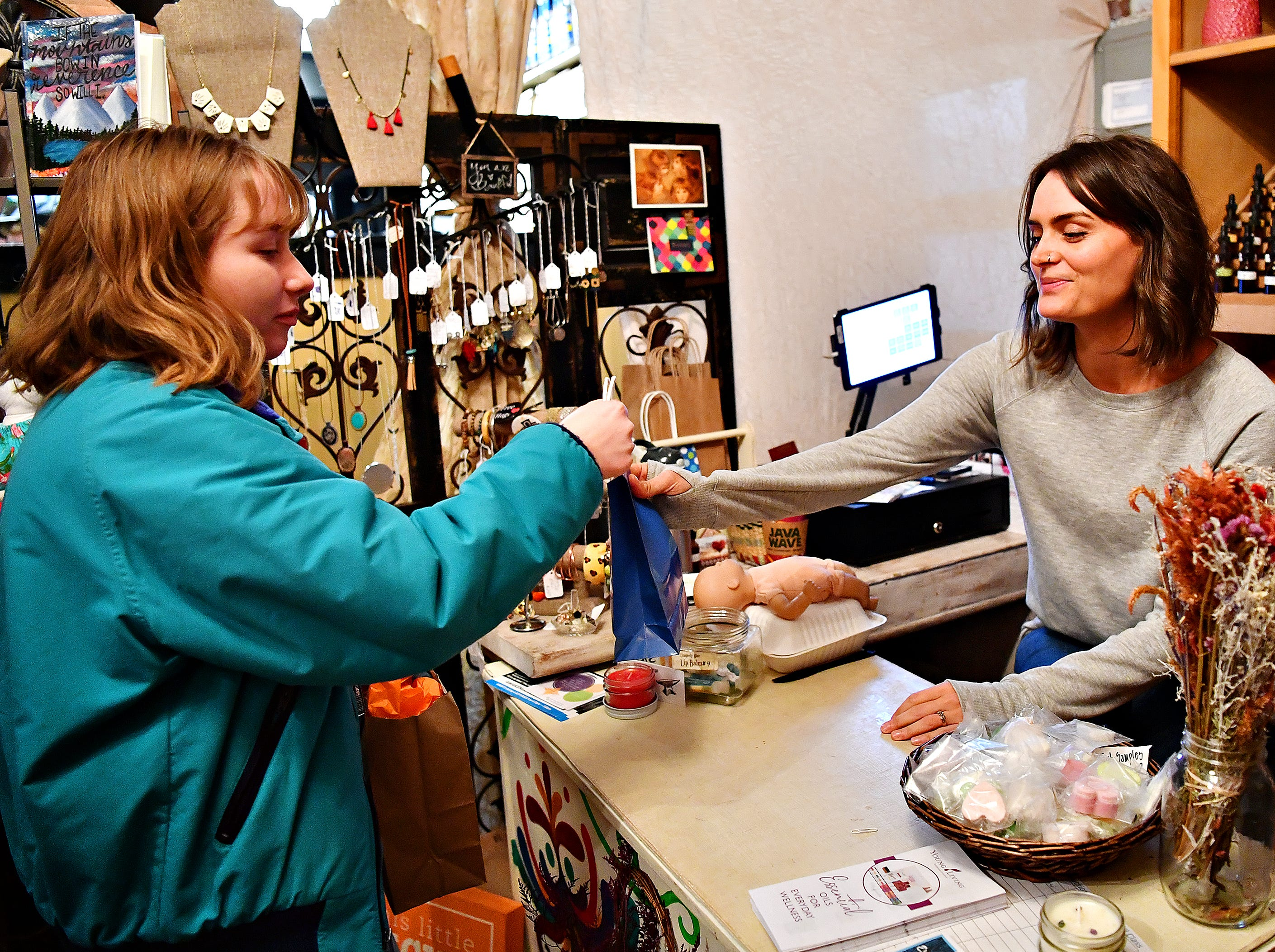 Store owner Lindsey Dohm, right, hands a shopping bag to Brooke Schwartz, 17, of York Township, at this little light of mine during Small Business Saturday at Central Market in York City, Saturday, Nov. 24, 2018. Dawn J. Sagert photo