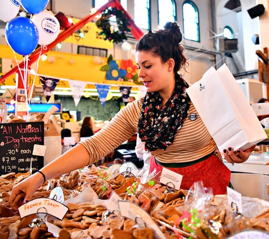 Owner of The Boys' Barking Bakery Meredith Lingenfelter, of Camp Hill, bags a customer's order during Small Business Saturday at Central Market in York City, Saturday, Nov. 24, 2018. Dawn J. Sagert photo