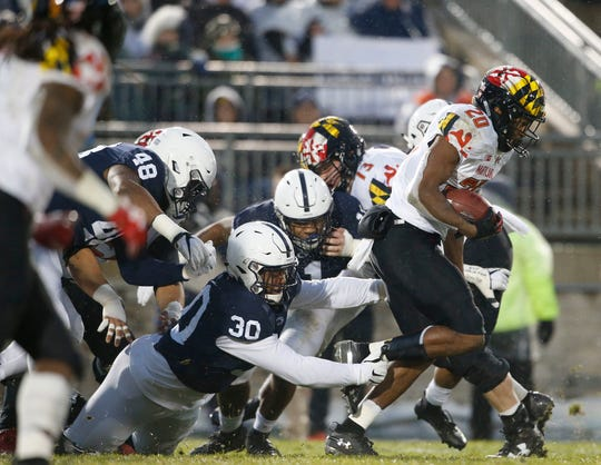 Maryland's Javon Leake (20) is tripped up by Penn State's Kevin Givens (30) during the first half of an NCAA college football game in State College, Pa., Saturday, Nov. 24, 2018.