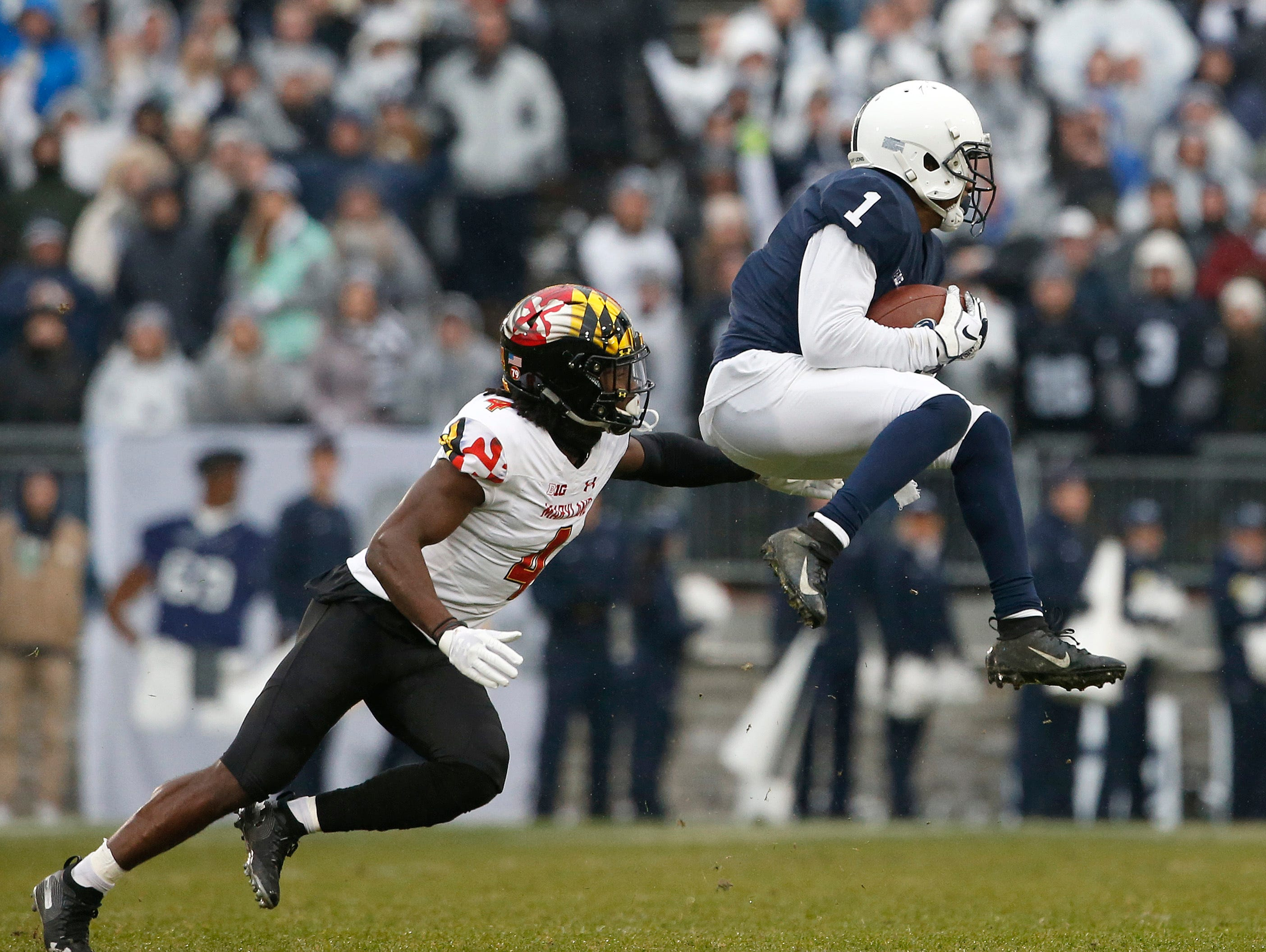 Penn State's KJ Hamler (1) catches a pass in front of Maryland's Darnell Savage Jr. (4) during the first half of an NCAA college football game in State College, Pa., Saturday, Nov. 24, 2018.