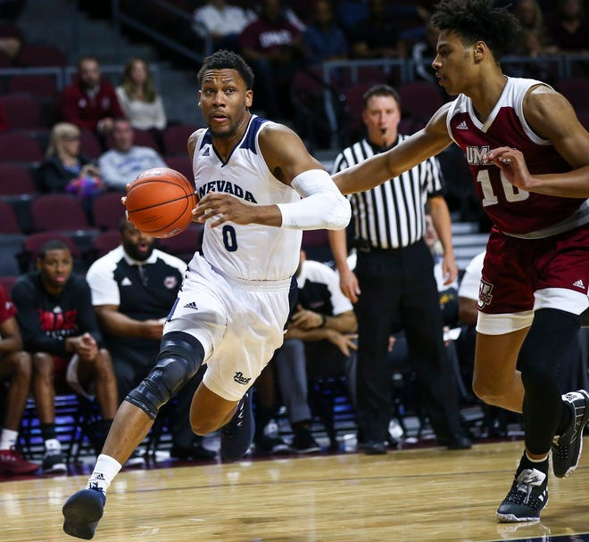 Nevada's Tre'Shawn Thurman (0) moves around Massachusetts' Sy Chatman  during the first half of Friday's Wolf Pack win.