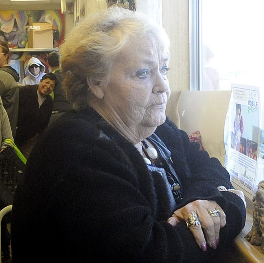 Silver Stage Food Pantry Coordinator Kathy McIntosh looks out the window at the line of clients waiting for food.