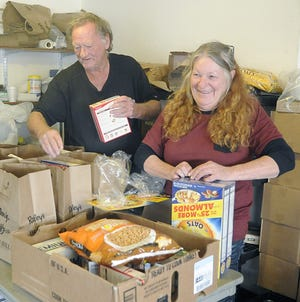 Volunteers Jeff Web and Mary Guthrie fill bags of food at the Yerington Food Pantry.