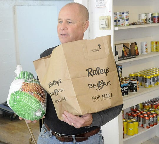 Yerington Food Pantry volunteer Jim Kusmerz carries food to a client's car.