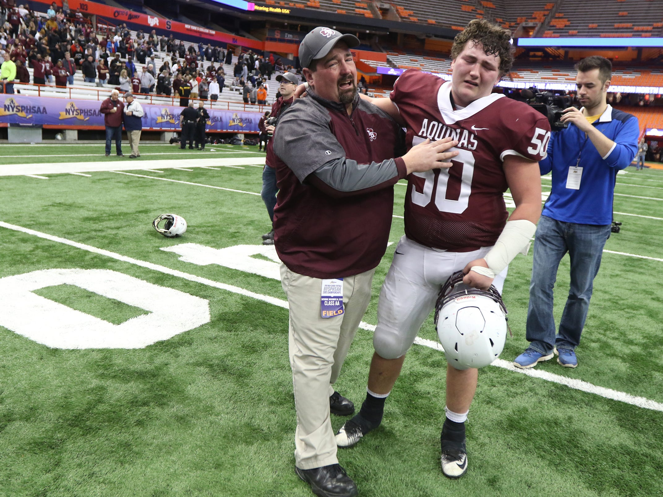 Aquinas Head Coach Derek Annechino and his son, Nick, who is a senior on the team, cry and celebrate the team's victory Saturday.