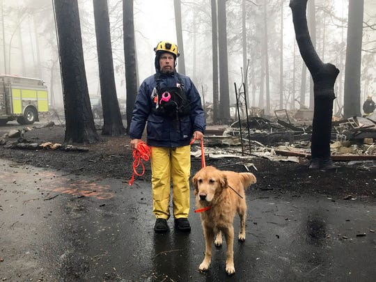 Eric Darling and his dog Wyatt are part of a search team from Orange County in Southern California who are among several teams conducting a second search of a mobile home park after the deadly Camp Fire in Paradise, Calif., Friday, Nov. 23, 2018. The team is doing a second search because there are still reports of missing people whose last known address was at the mobile home park. They look for clues that may indicate someone couldn't get out, such as a car in the driveway or a wheelchair ramp.
