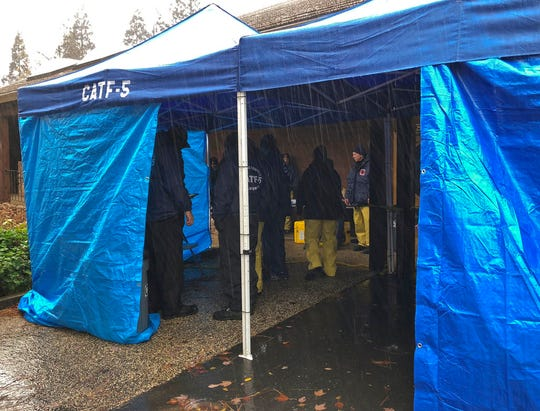 National Urban Search & Rescue Response System Orange County CATF-5 team members take cover from the rain in Paradise, Calif., Friday, Nov. 23, 2018. High winds and heavy rains temporarily halted the work of some search teams out looking for remains of people caught up in the deadly wildfire. The Camp Fire, which destroyed the historical mining town of Paradise, is the most deadly wildfire in state history, with 84 fatalities as of Friday, according to statistics from the California Department of Forestry and Fire Protection. It's also the deadliest in the U.S. in a century.