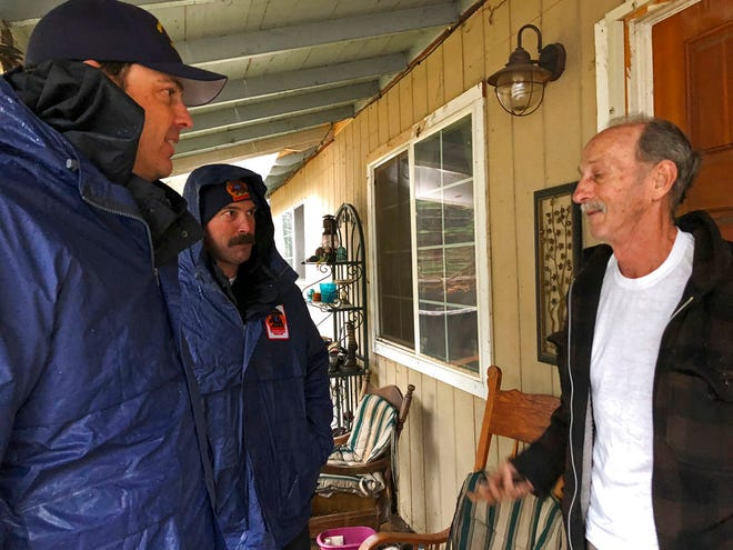 Craig Covey, task force leader for the Orange County search team, left, with David Harper, middle, talk to resident Stewart Nugent outside his Paradise home on Friday, Nov. 23, 2018. Covey and several team members took two giant brown bags full of lunch to 64-year-old Nugent, who stayed in his home and fought off flames. Rough is among the thousands of people whose homes burned down when the deadly wildfire ripped through Paradise and surrounding communities. At least 84 people died, and more than 13,000 homes were destroyed.