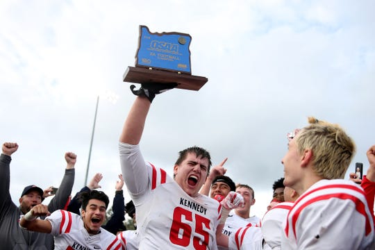 Kennedy's Nick Suing (No. 65) holds the 2A state championship trophy