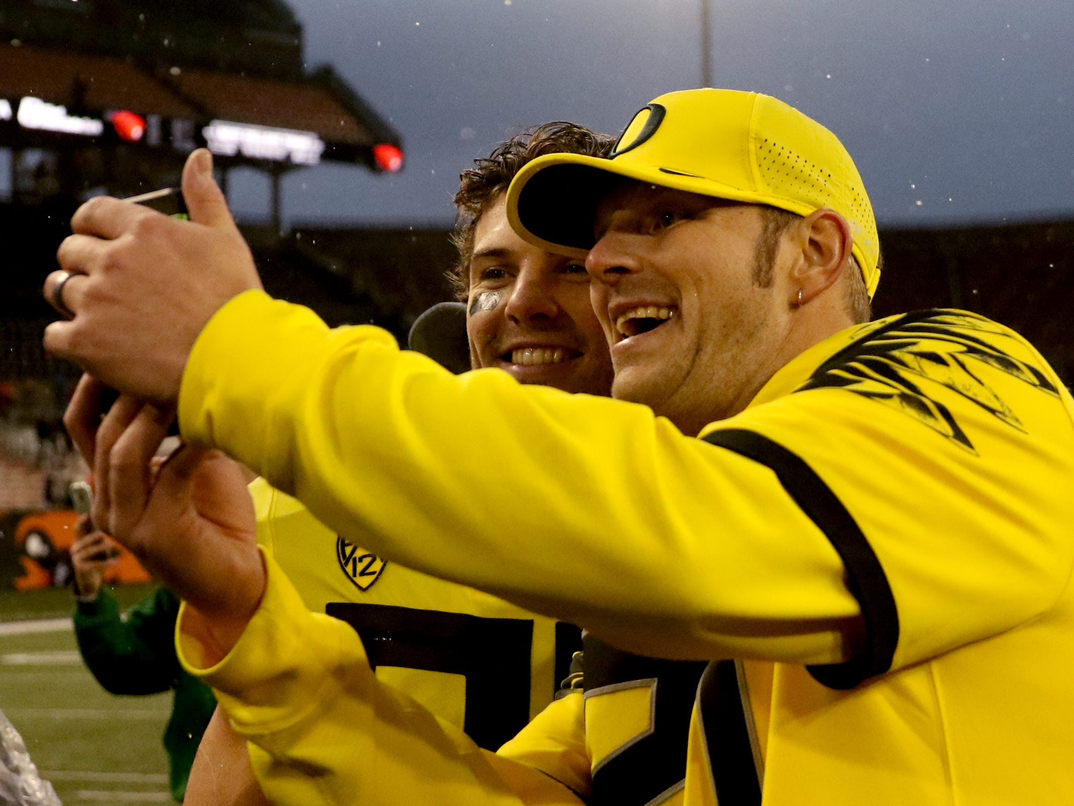 Ducks fans Kevin Case takes a photo with Oregon's Brady Breeze (25) following the Oregon vs. Oregon State Civil war football game at Oregon State University in Corvallis on Friday, Nov. 23, 2018. The Ducks won the game 55-15.