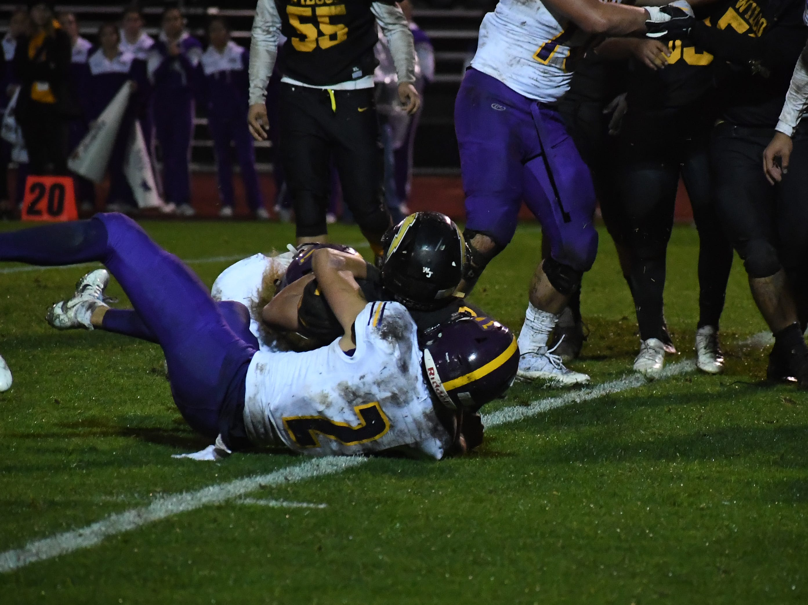 Linebacker Nick Marquez and safety Zachary Robison (2) tackles a Wilcox ball-carrier.
