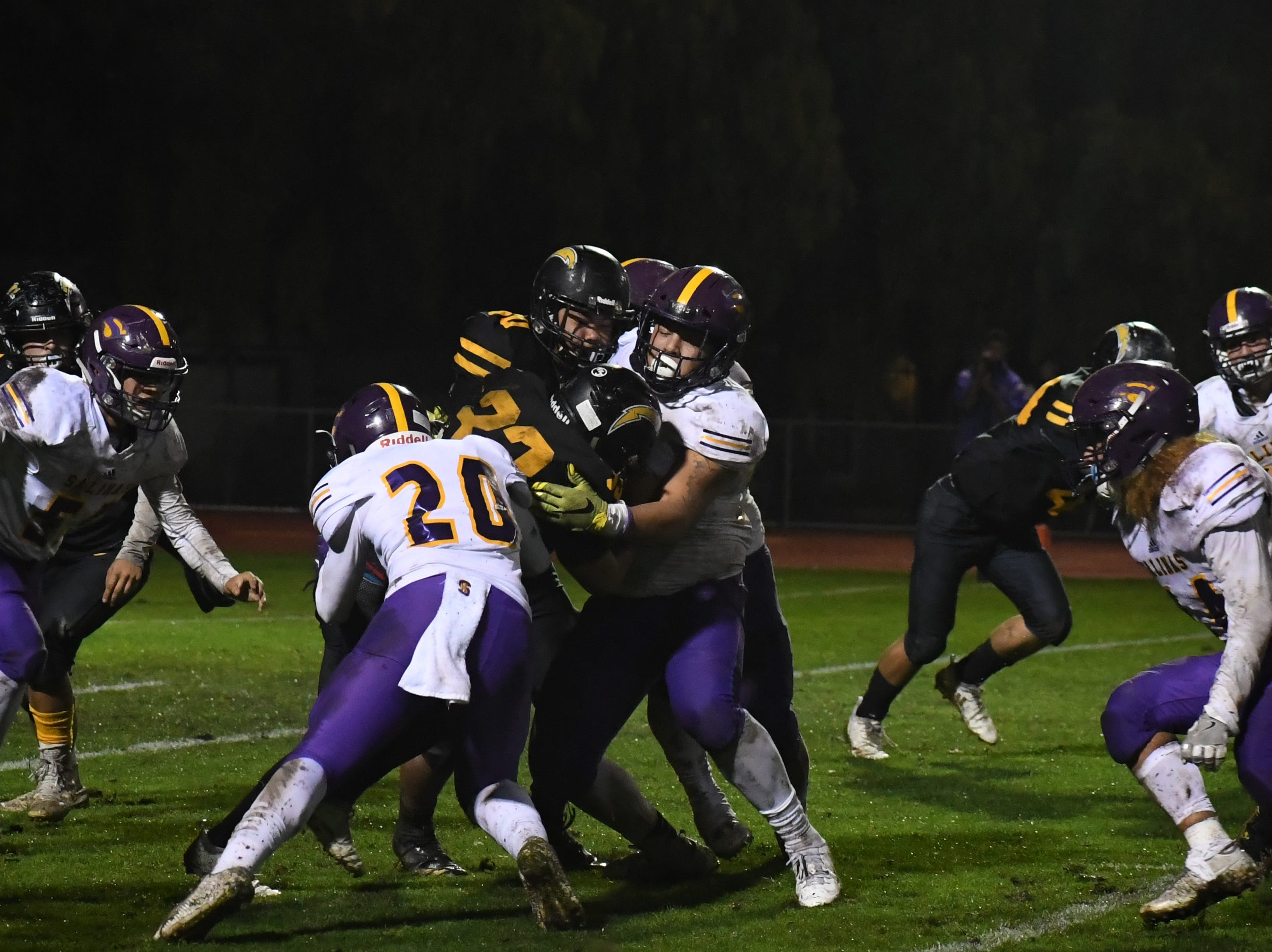 Salinas defensive lineman Sebastian Gomez (57) and linebacker Joey Moag (20) wrap up a Wilcox running back.