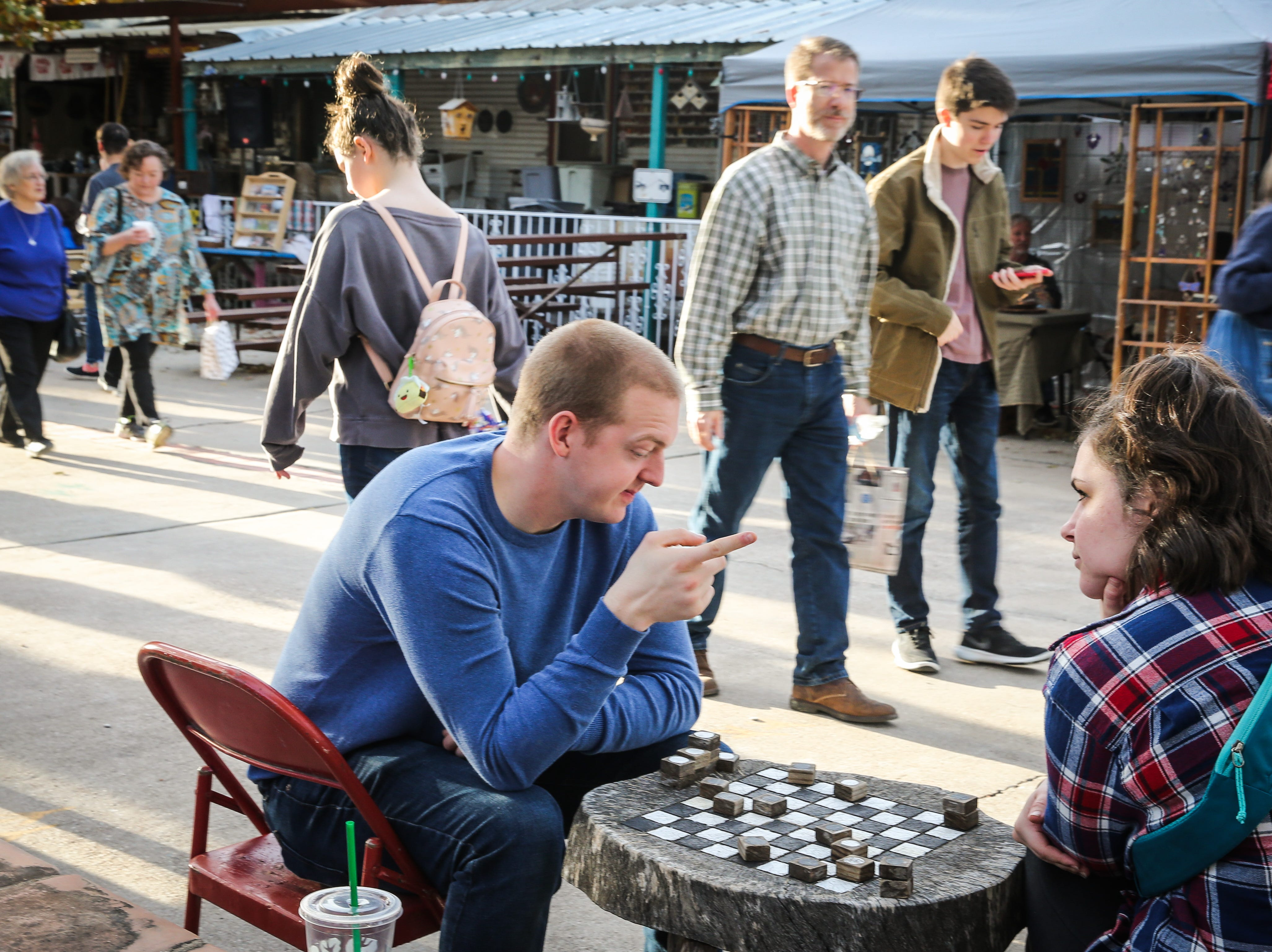 Adam Bailey and Kassidy Currence play checkers wile visitors walk around during the Thanksgiving Open House Friday, Nov. 23, 2018, at the Chicken Farm Art Center.