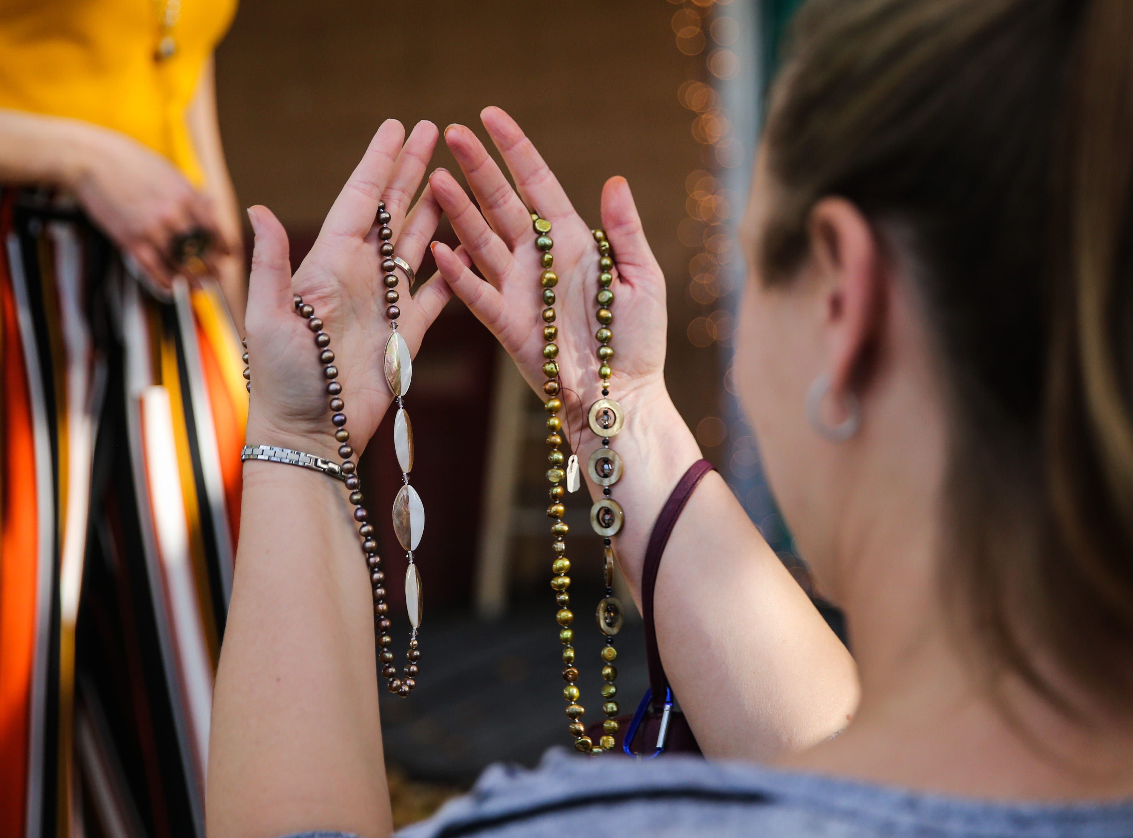 Lindsay Harrison compares necklaces during the Thanksgiving Open House Friday, Nov. 23, 2018, at the Chicken Farm Art Center.
