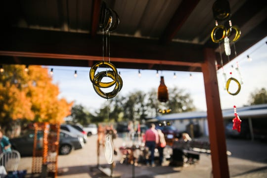 Wind chimes are lit by the sunlight as visitors walk around the booths during the Thanksgiving Open House Friday, Nov. 23, 2018, at the Chicken Farm Art Center.
