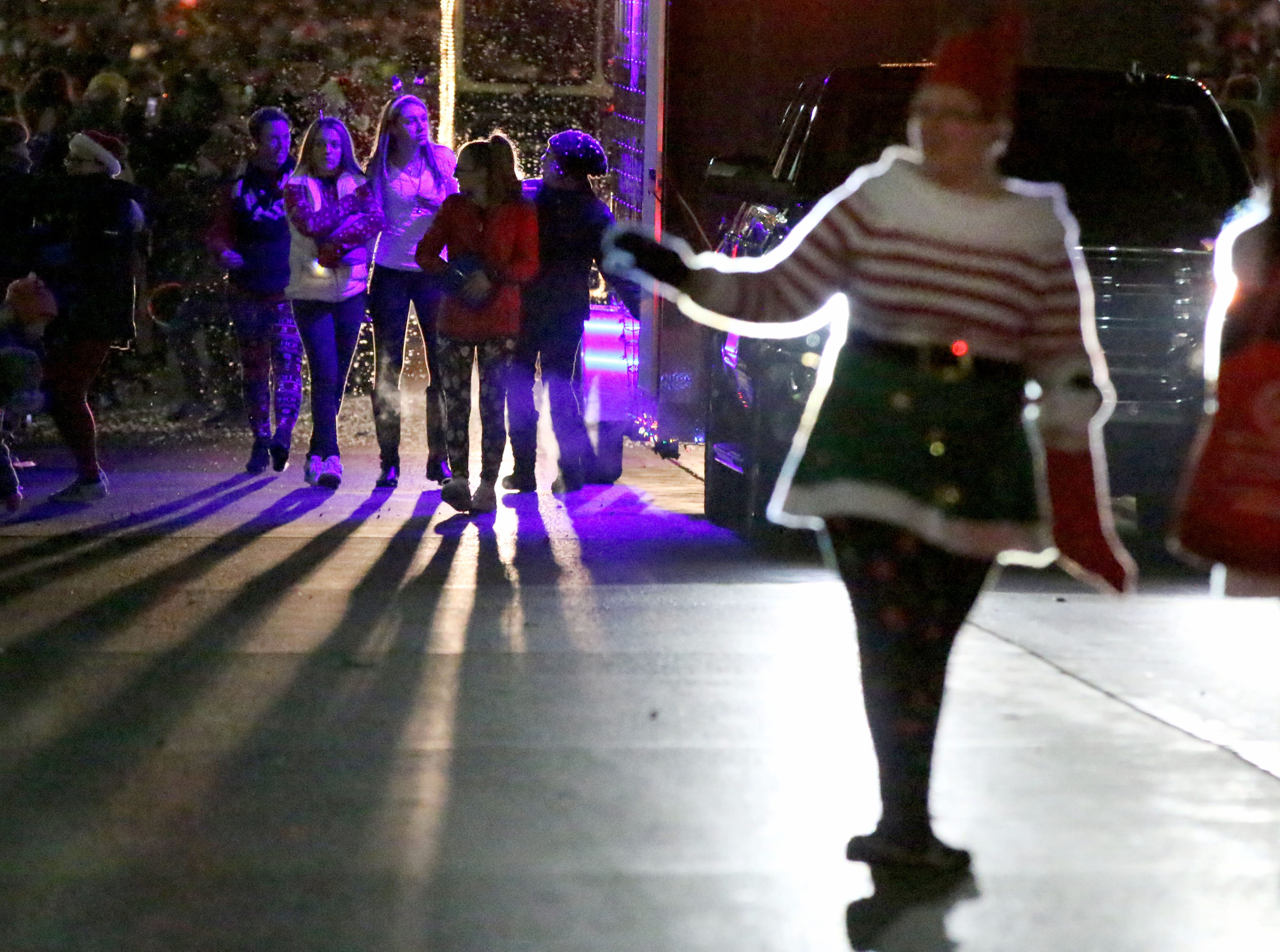 Lights of all colors illuminate people at the Plymouth Christmas Parade, Friday, November 23, 2018, in Plymouth, Wis.