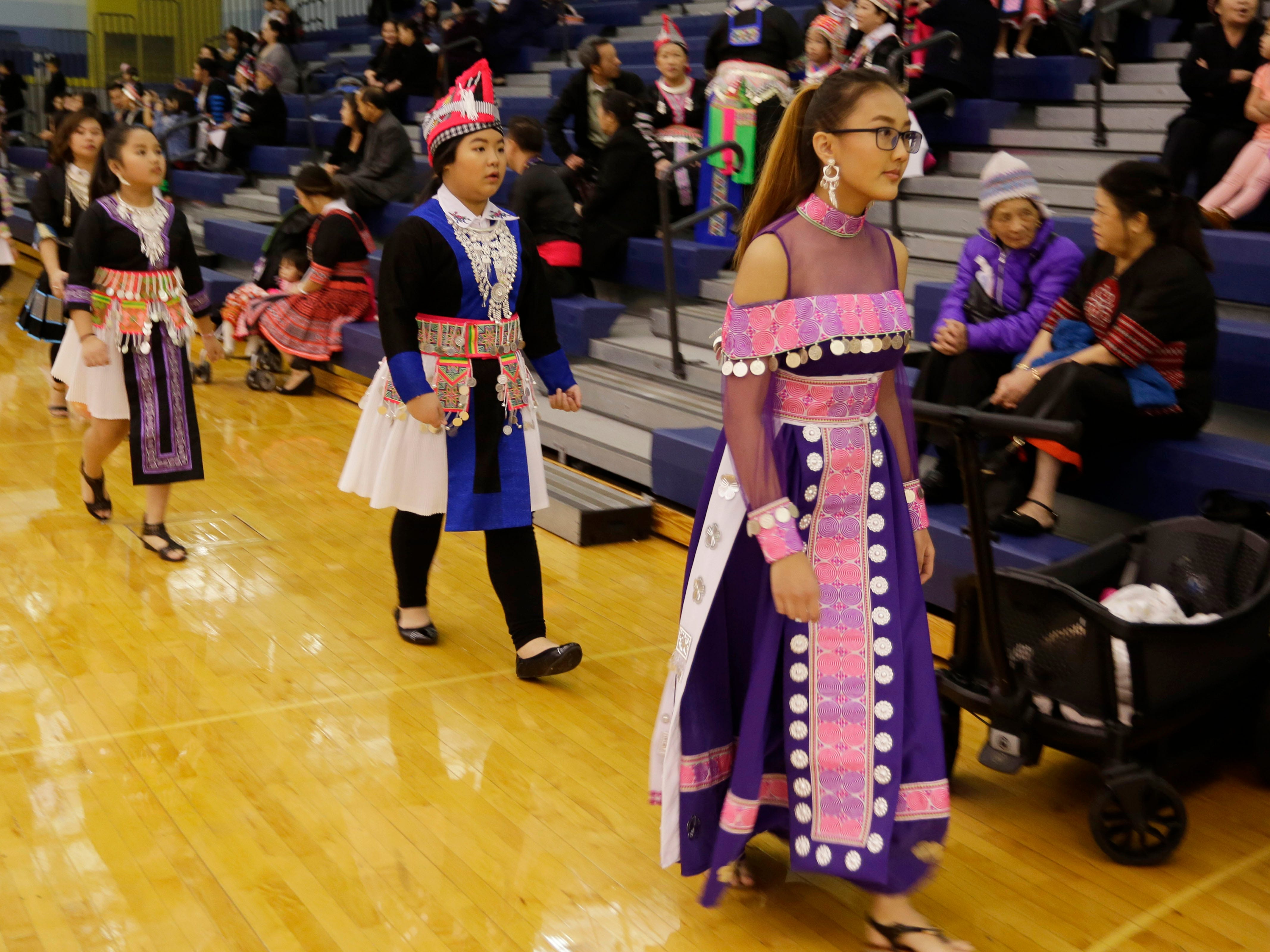 Hmong fashion contestants walk by the crowd at Sheboygan North High School, Saturday, November 24, 2018, in Sheboygan, Wis.