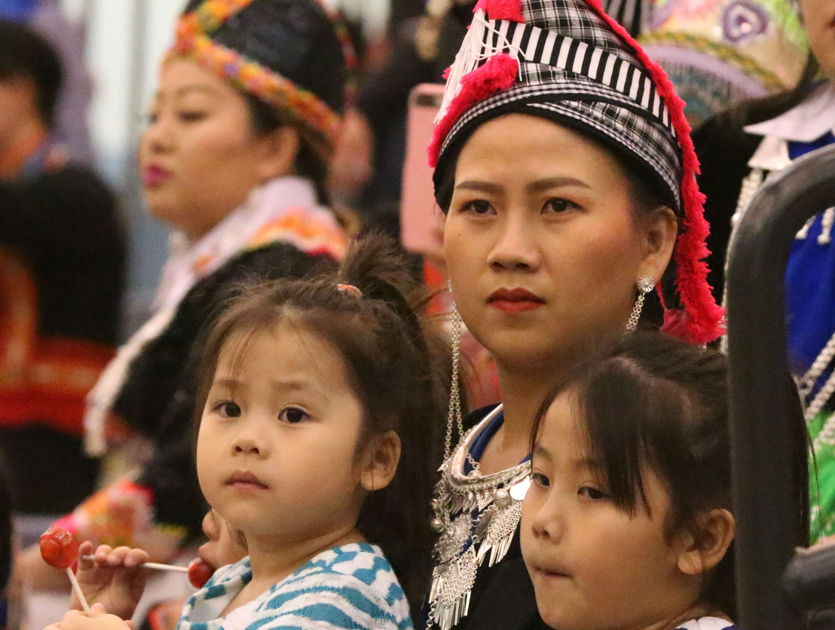 A family watches dancing during the Hmong New Year event held at Sheboygan North High School, Saturday, November 24, 2018, in Sheboygan, Wis.