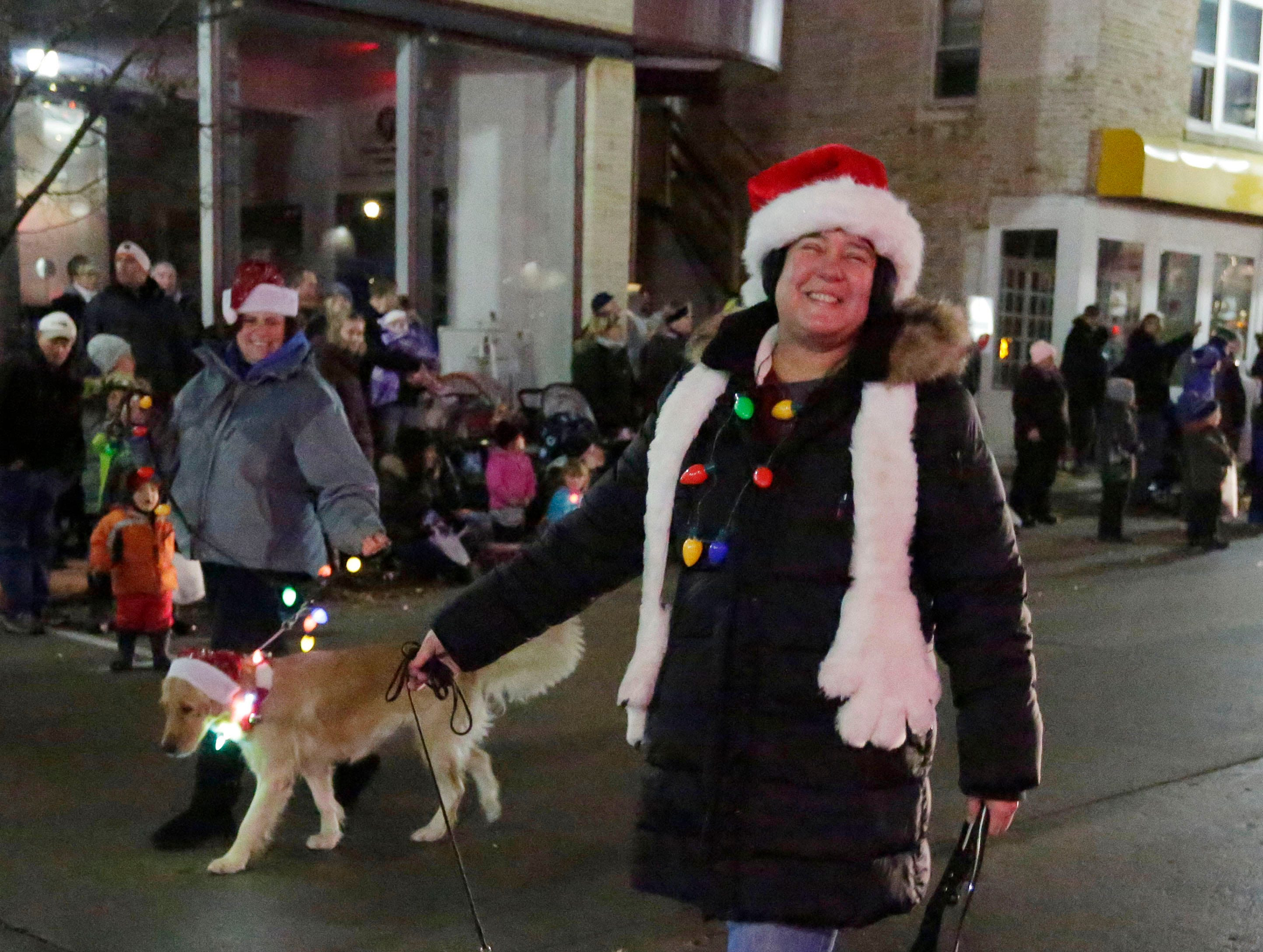 Sue Dempster of Sheboygan Falls smiles with her dogs who were decorated with holiday lights in the Plymouth Christmas Parade, Friday, November 23, 2018, in Plymouth, Wis.