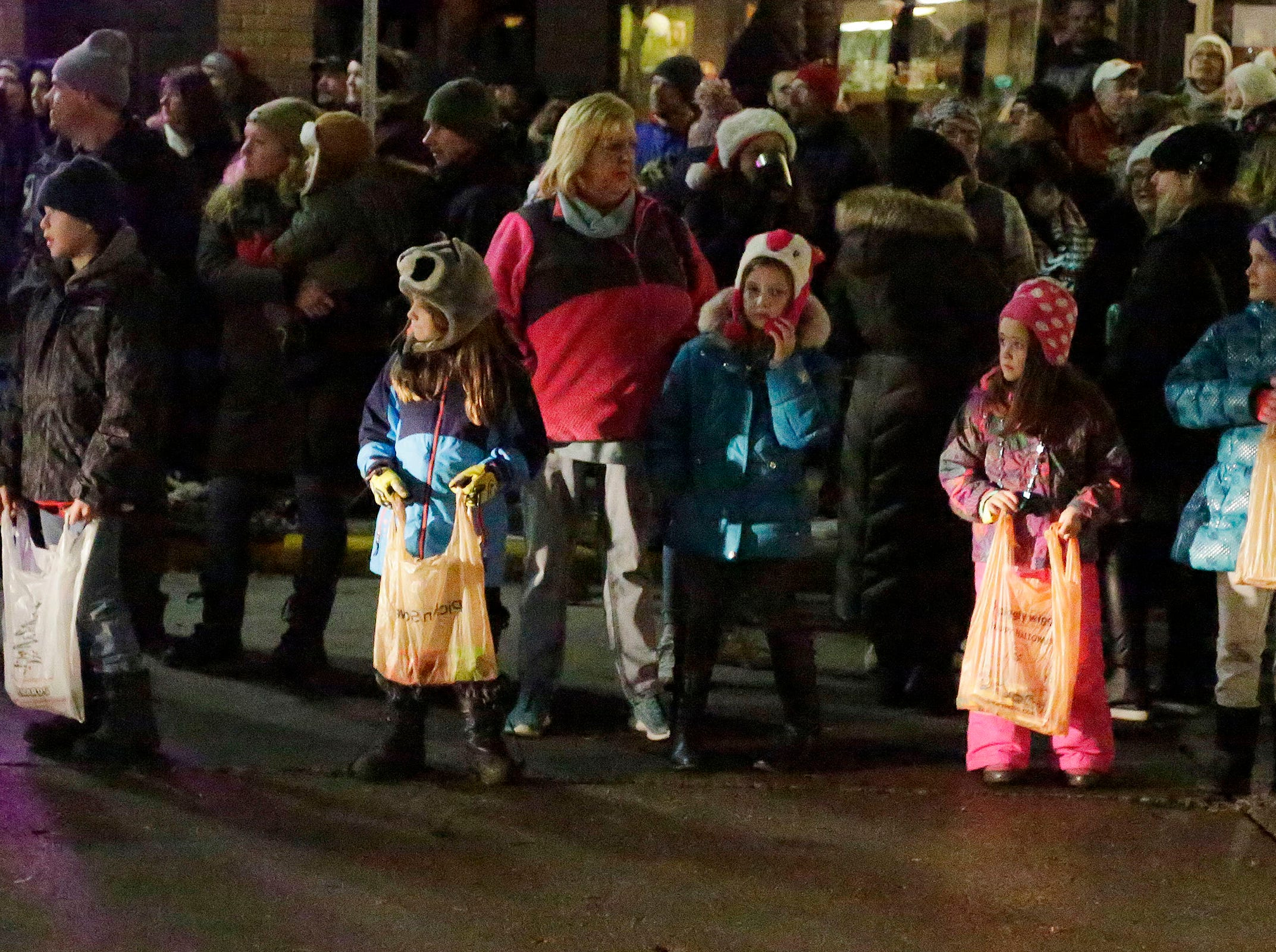 Children wait with bags for candy at the Plymouth Christmas Parade, Friday, November 23, 2018, in Plymouth, Wis.