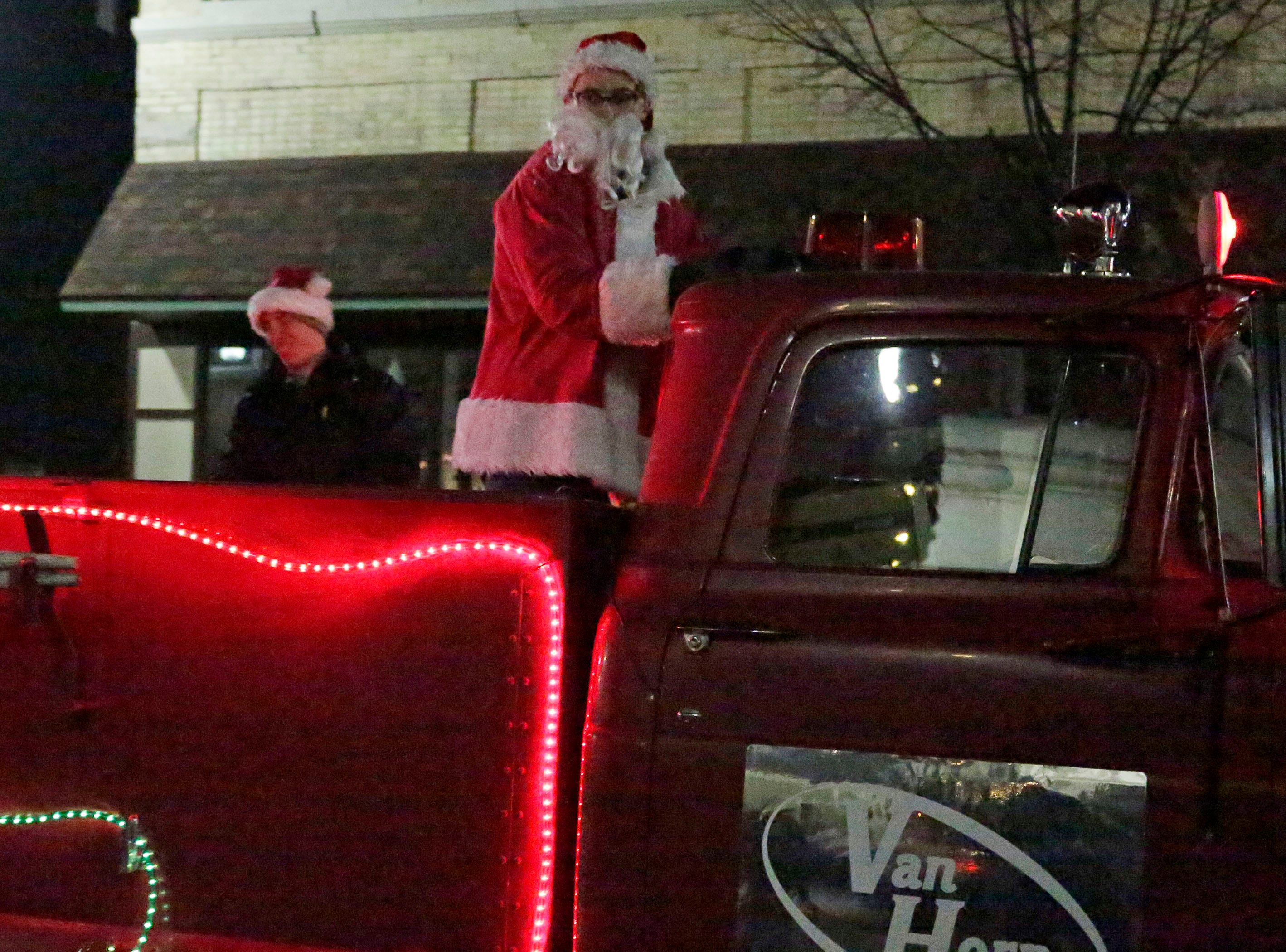 Santa Claus commands a fire truck in the Plymouth Christmas Parade, Friday, November 23, 2018, in Plymouth, Wis.