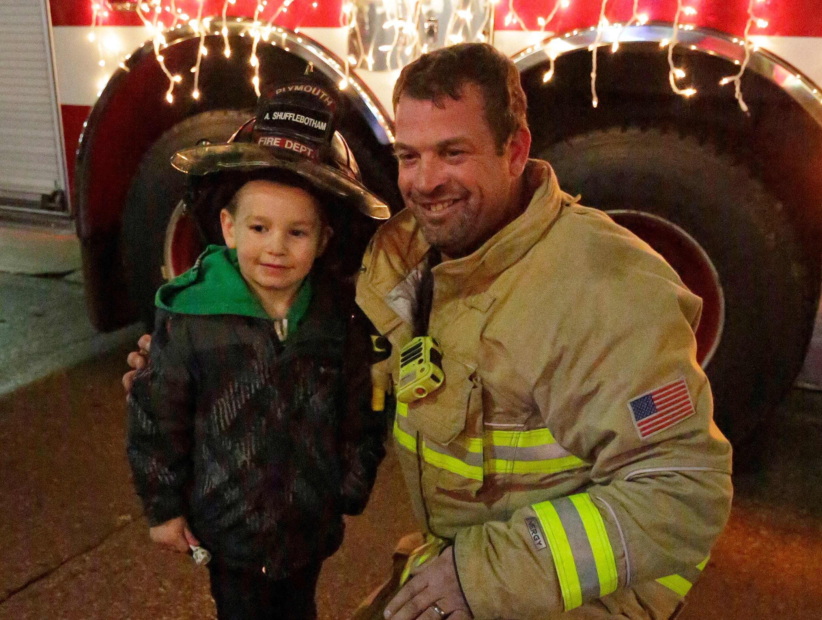 Finnegan Brusky, 5, of Plymouth poses with Plymouth firefighter Andrew Shufflebotham following the Plymouth Christmas Parade, Friday, November 23, 2018, in Plymouth, Wis.
