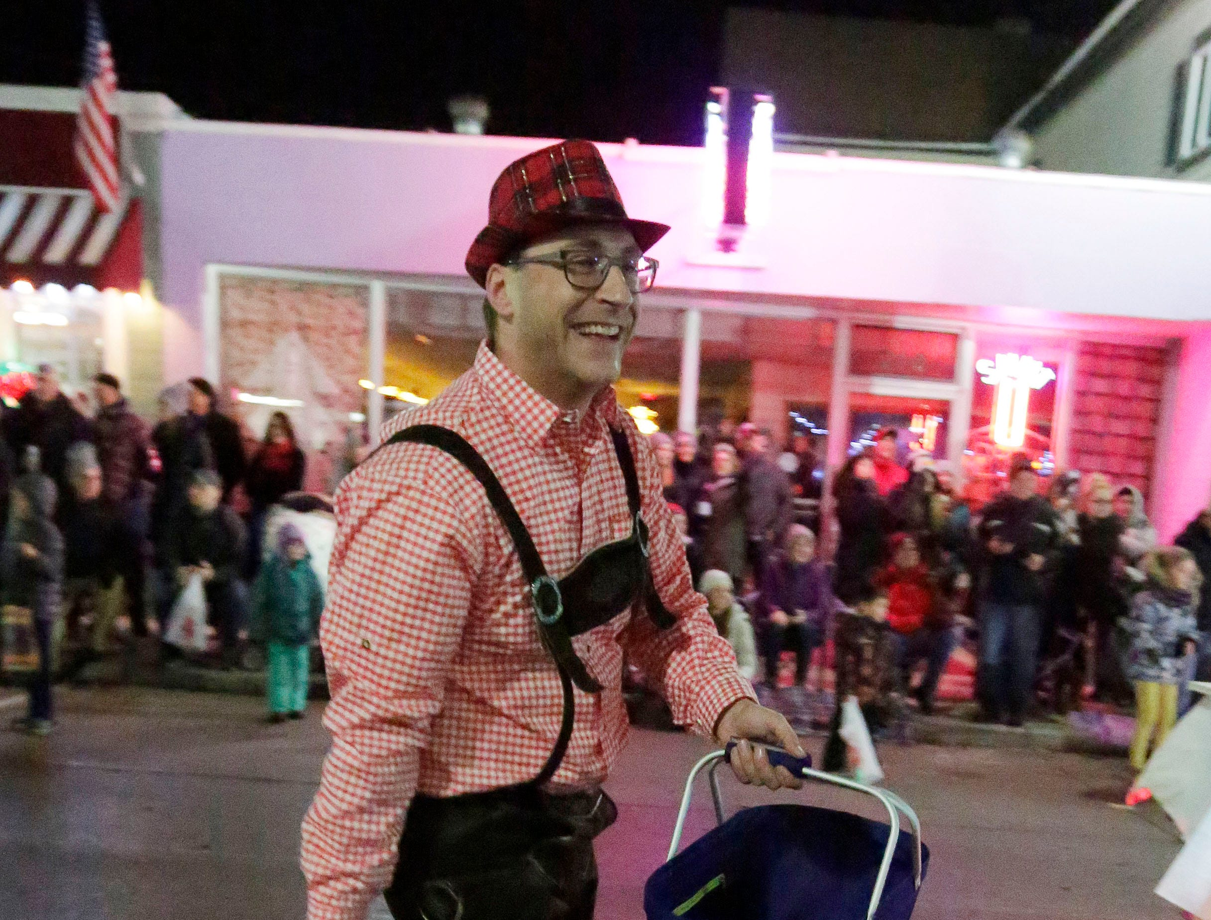 A man wearing lederhosen tosses string cheese to people along the Plymouth Christmas Parade route, Friday, November 23, 2018, in Plymouth, Wis.