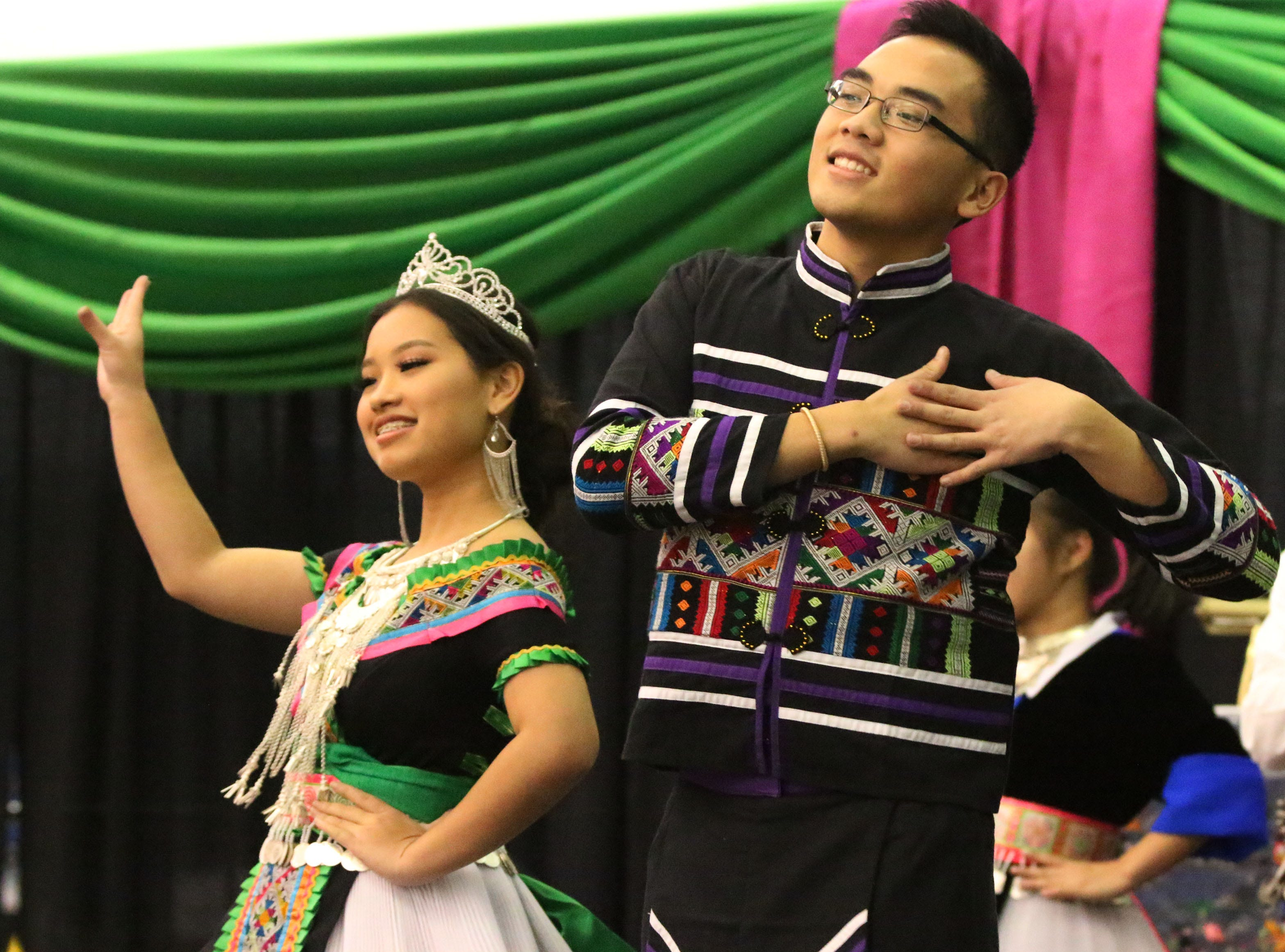 Hmong dancers gesture while dancing in competition during the Hmong New Year at Sheboygan North High School, Saturday, November 24, 2018, in Sheboygan, Wis.