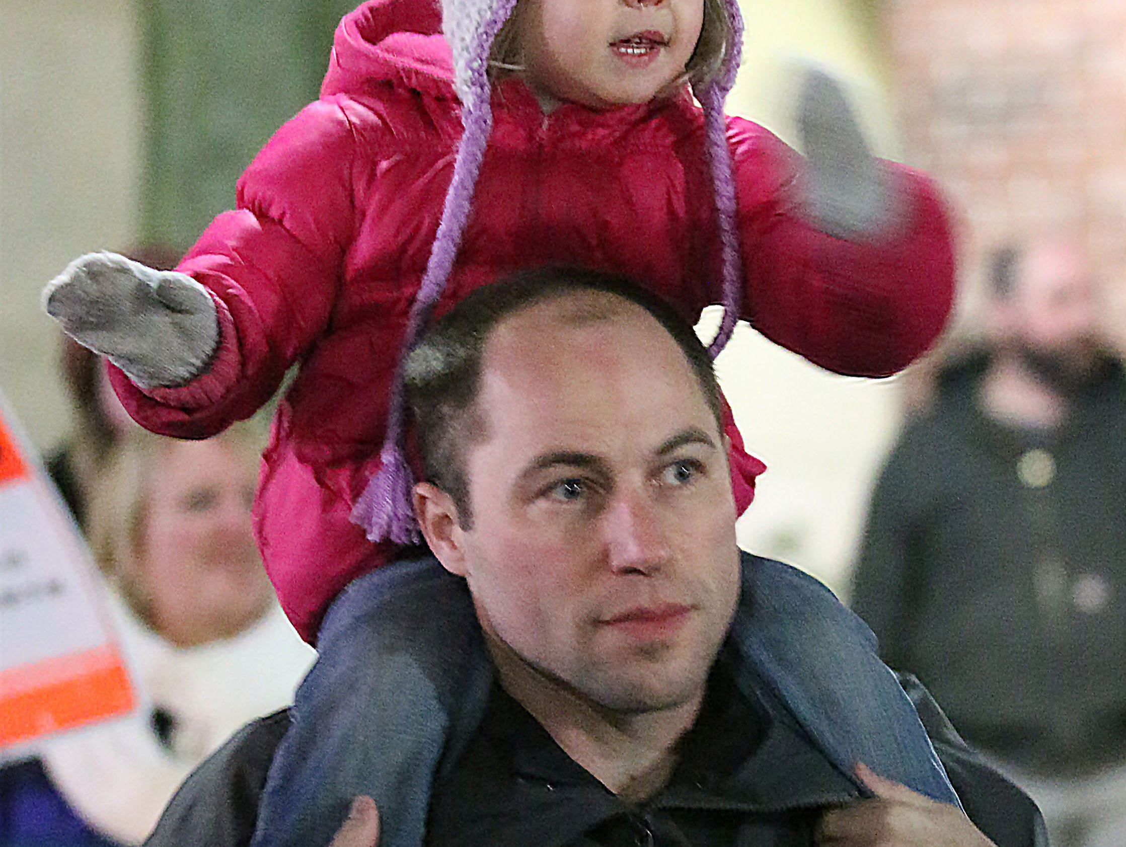 Breanna Otte, 2, waves to the parade from atop her dad Jon's shoulders at the Plymouth Christmas Parade, Friday, November 23, 2018, in Plymouth, Wis.