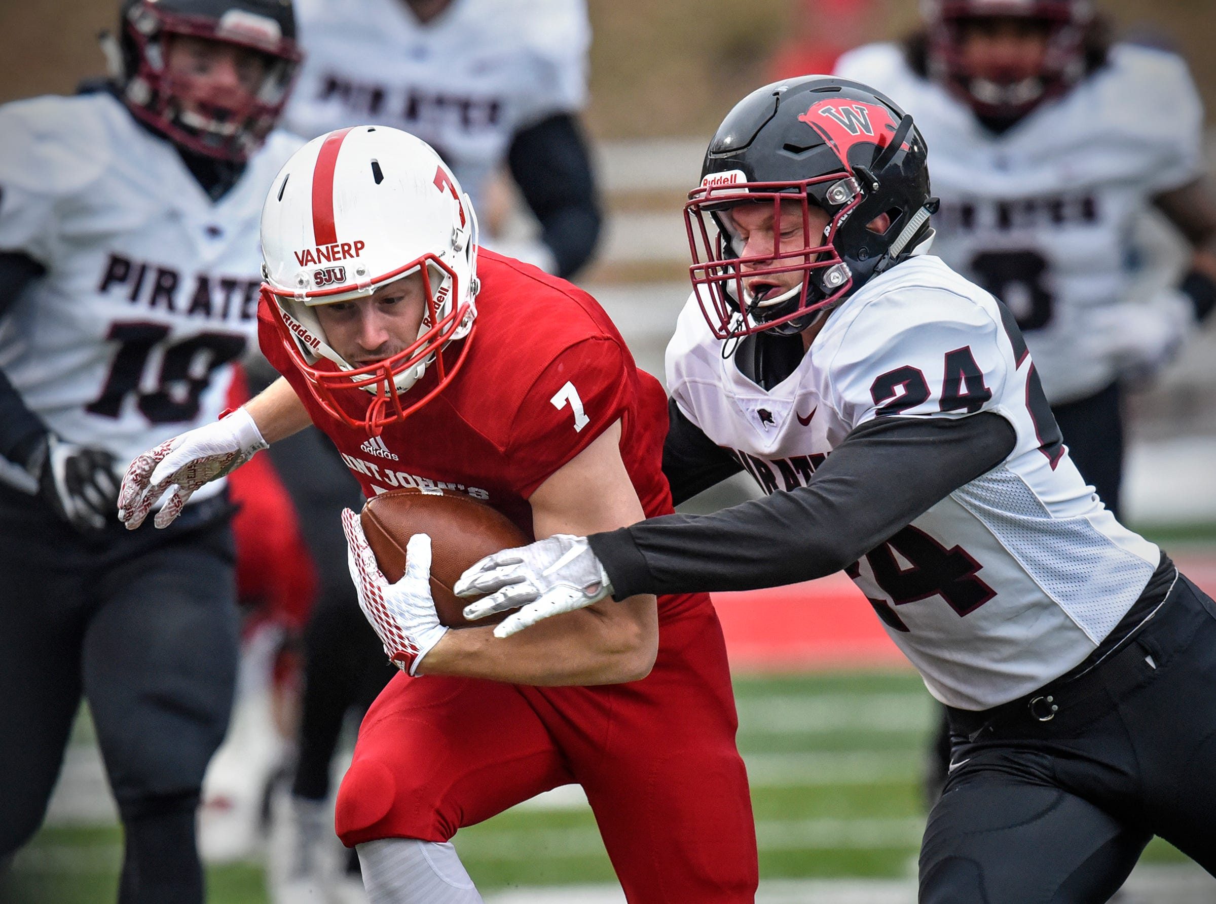 Wide receiver Andrew VanErp of St. John's tries to escape a tackle by Zach Hillman of Whitworth during the Saturday, Nov. 24, game at Clemens Stadium in Collegeville.