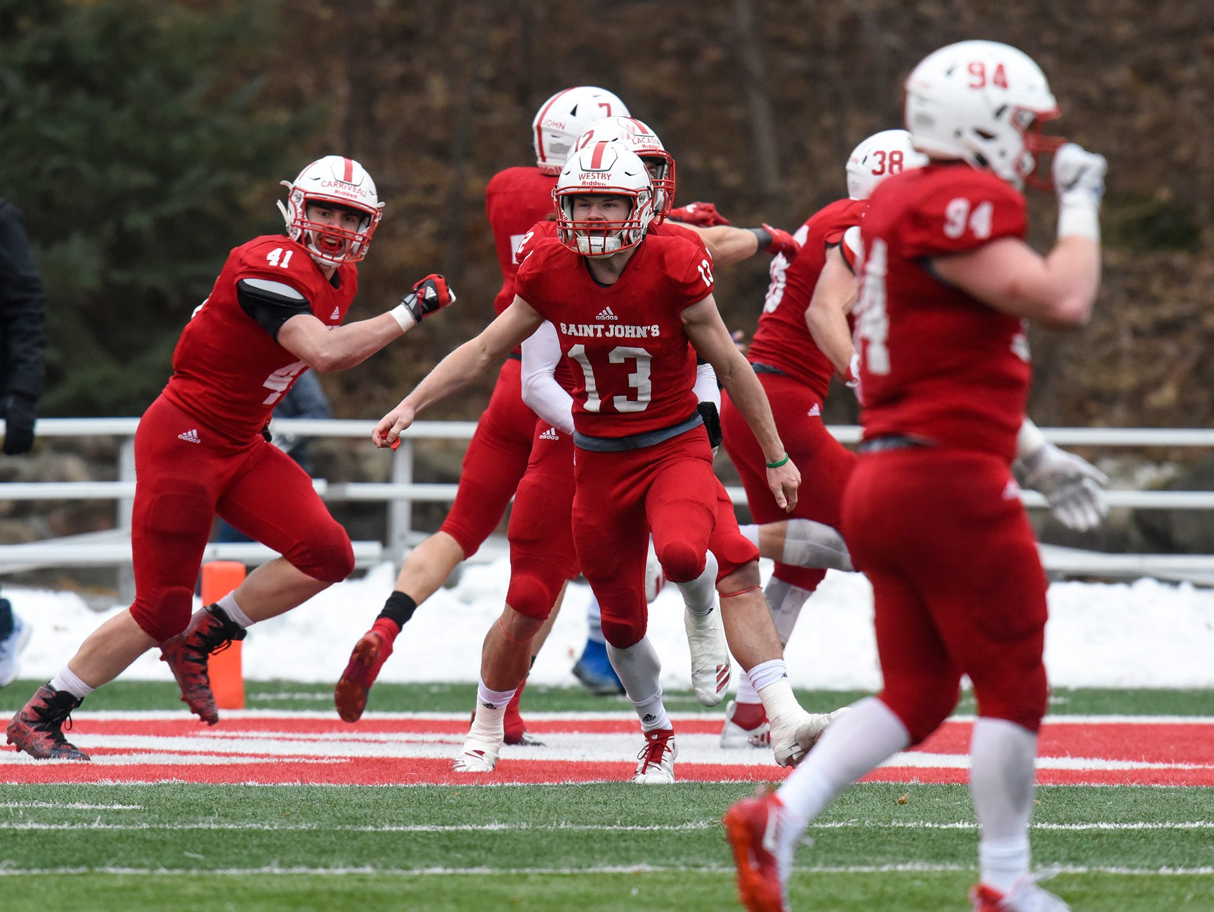 St. John's players celebrate a touchdown during the Saturday, Nov. 24, game against Whitworth at Clemens Stadium in Collegeville.