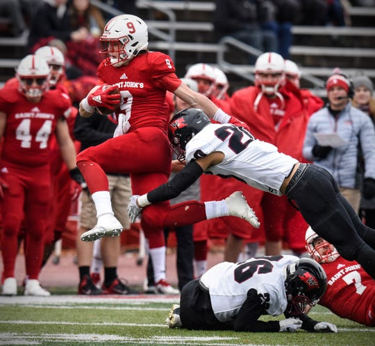 Will Gillach leaps for a gain for St. John's during the Saturday, Nov. 24, game against Whitworth at Clemens Stadium in Collegeville.