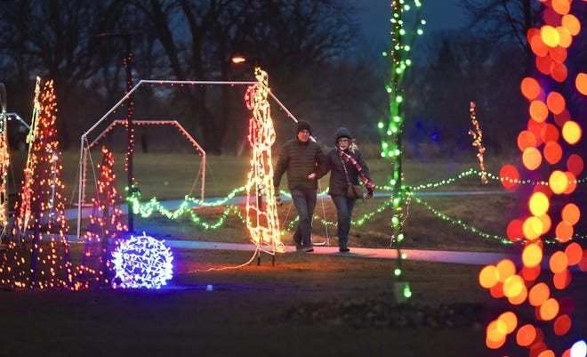 Walkers stroll around the lake on the lighted trail at the Country Lights Festival near the Sartell Community Center in this 2017 photo. Thousands of lights mark the trail.