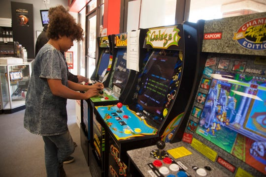 Customers play arcade games at Comics Plus in St. George on Small Business Saturday, Nov. 24, 2018.