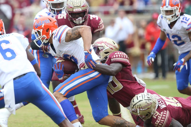 Florida Gators wide receiver Freddie Swain (16) fights off a tackle from Florida State Seminoles defensive back Calvin Brewton (10) as the Florida State Seminoles take on their rival the Florida Gators in college football at Doak S. Campbell Stadium, Saturday, Nov. 24, 2018.
