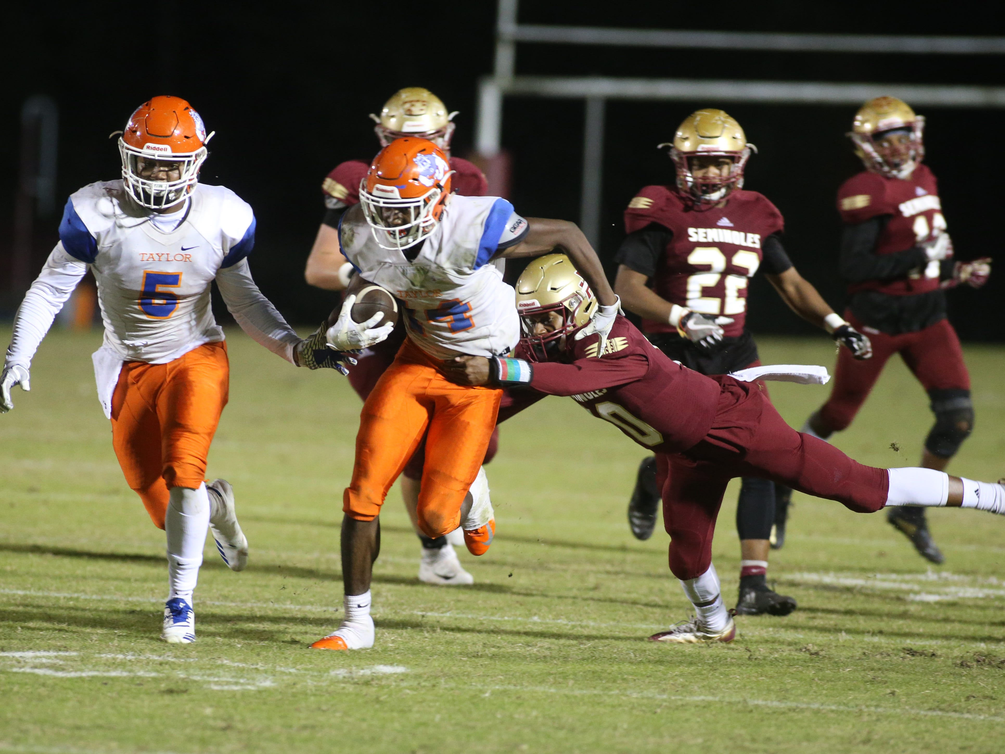 Taylor County wide receiver Robert Glanton (14) fights off a Florida High defender during a Region 1-3A final on Friday, Nov. 23, 2018.