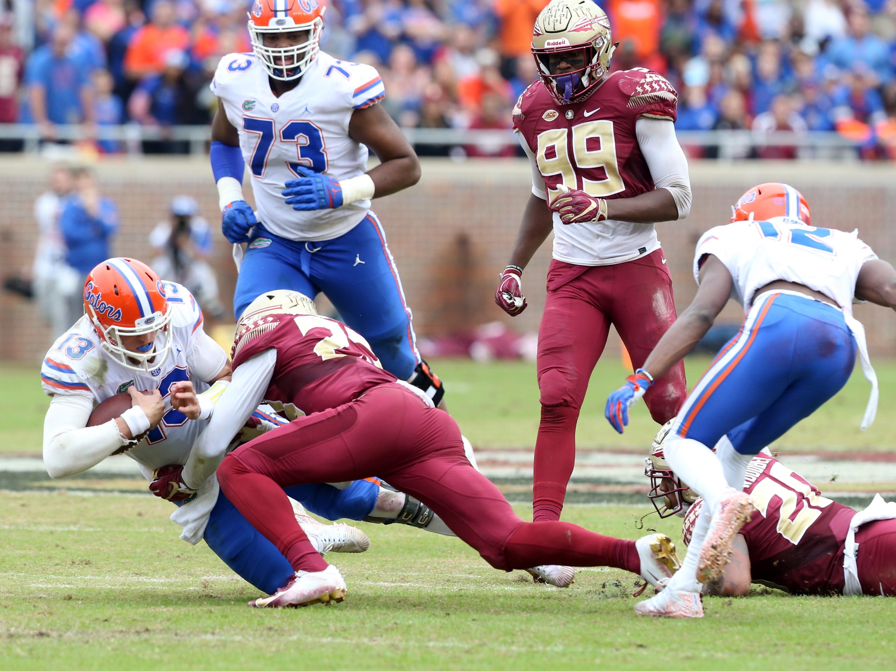 Florida Gators quarterback Feleipe Franks (13) gets taken down by the Seminole defense as the Florida State Seminoles take on their rival the Florida Gators in college football at Doak S. Campbell Stadium, Saturday, Nov. 24, 2018.