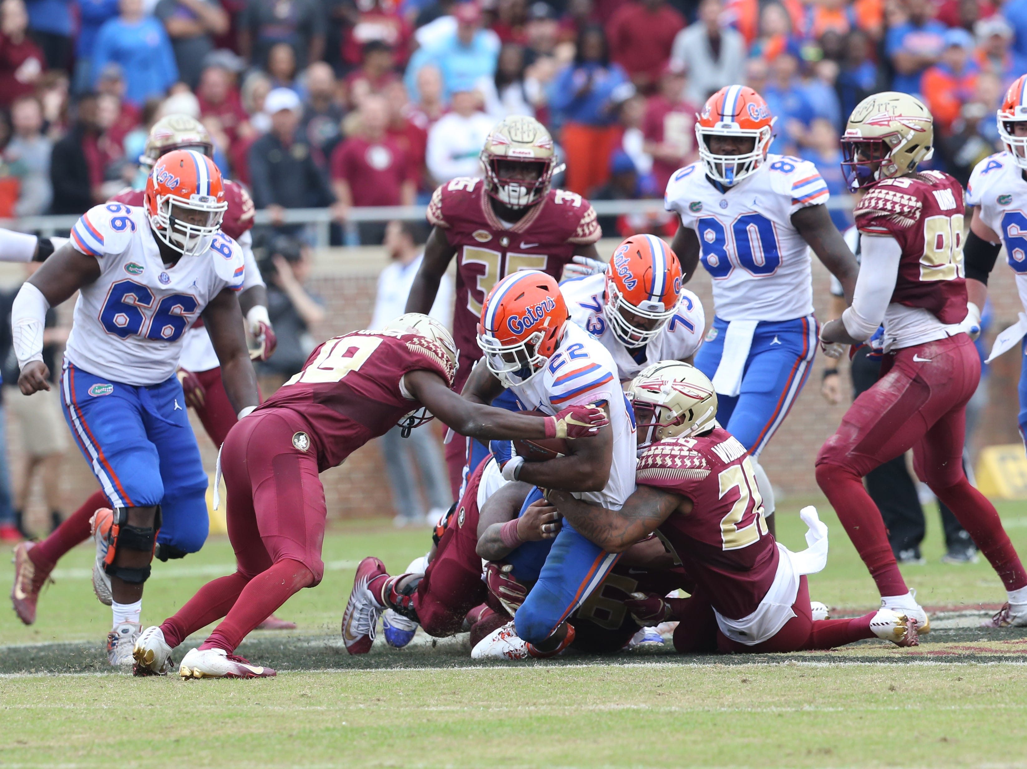 Florida Gators running back Lamical Perine (22) gets taken down by the Seminole defense as the Florida State Seminoles take on their rival the Florida Gators in college football at Doak S. Campbell Stadium, Saturday, Nov. 24, 2018.
