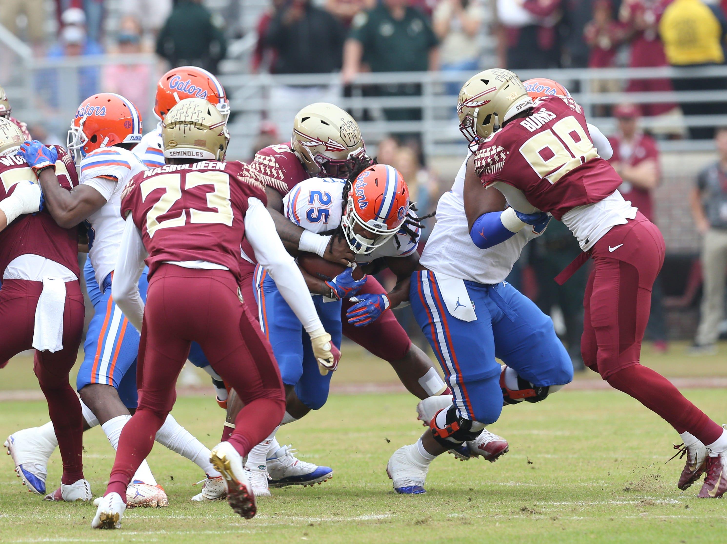 Florida Gators running back Jordan Scarlett (25) fights off the defense as the Florida State Seminoles take on their rival the Florida Gators in college football at Doak S. Campbell Stadium, Saturday, Nov. 24, 2018.