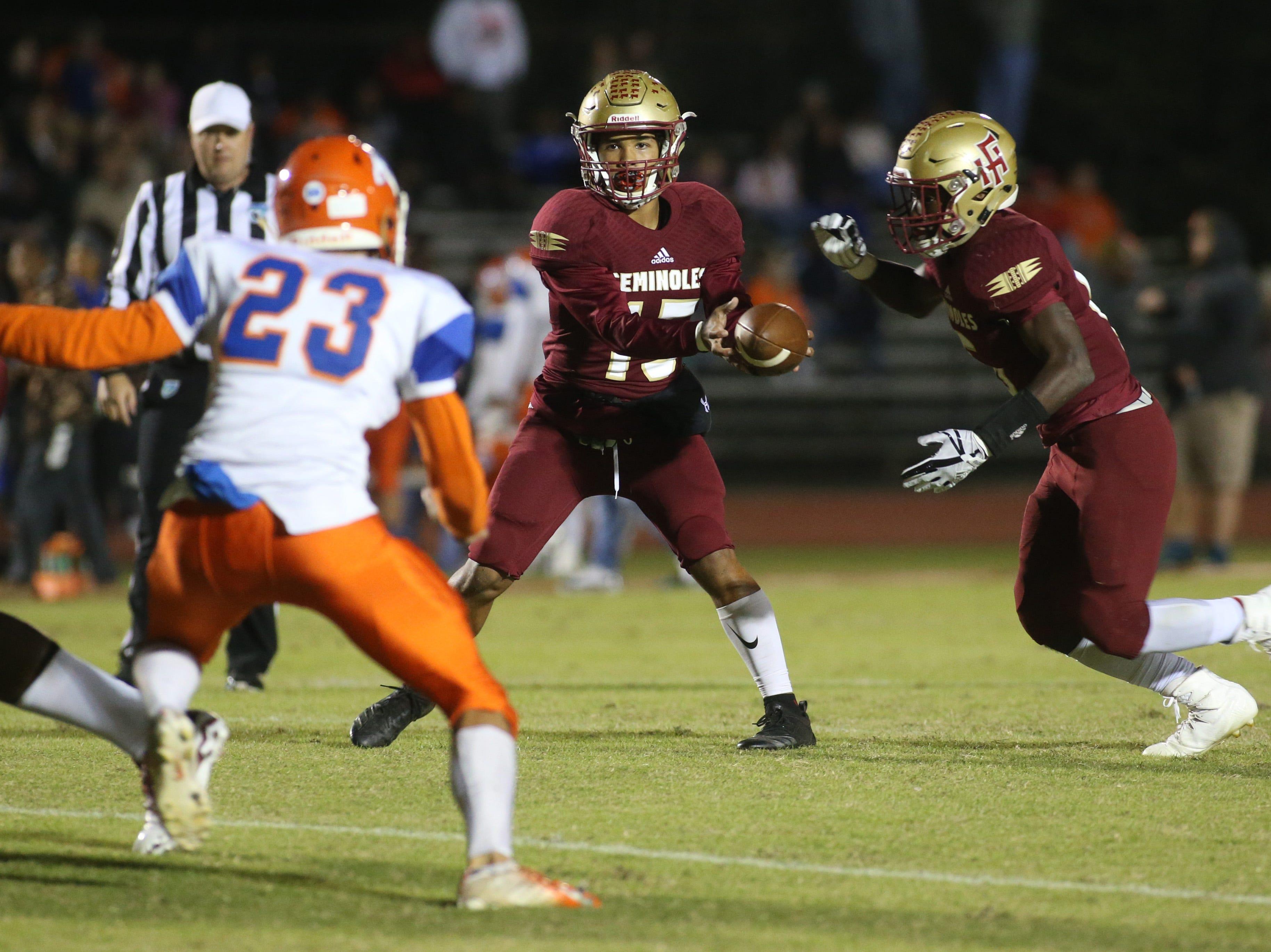 Florida High Seminole quarterback Bryson Hill (15) hands off the ball as the Taylor County Bulldogs play the Florida High Seminoles in a Region 1-3A final on Friday, Nov. 23, 2018.