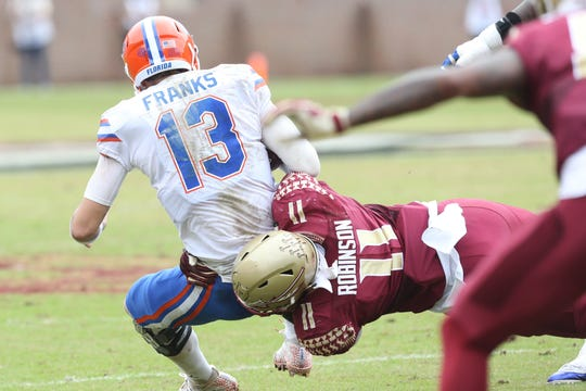 Florida Gators quarterback Feleipe Franks (13) gets tackled by Florida State Seminoles defensive end Janarius Robinson (11) as the Florida State Seminoles take on their rival the Florida Gators in college football at Doak S. Campbell Stadium, Saturday, Nov. 24, 2018.