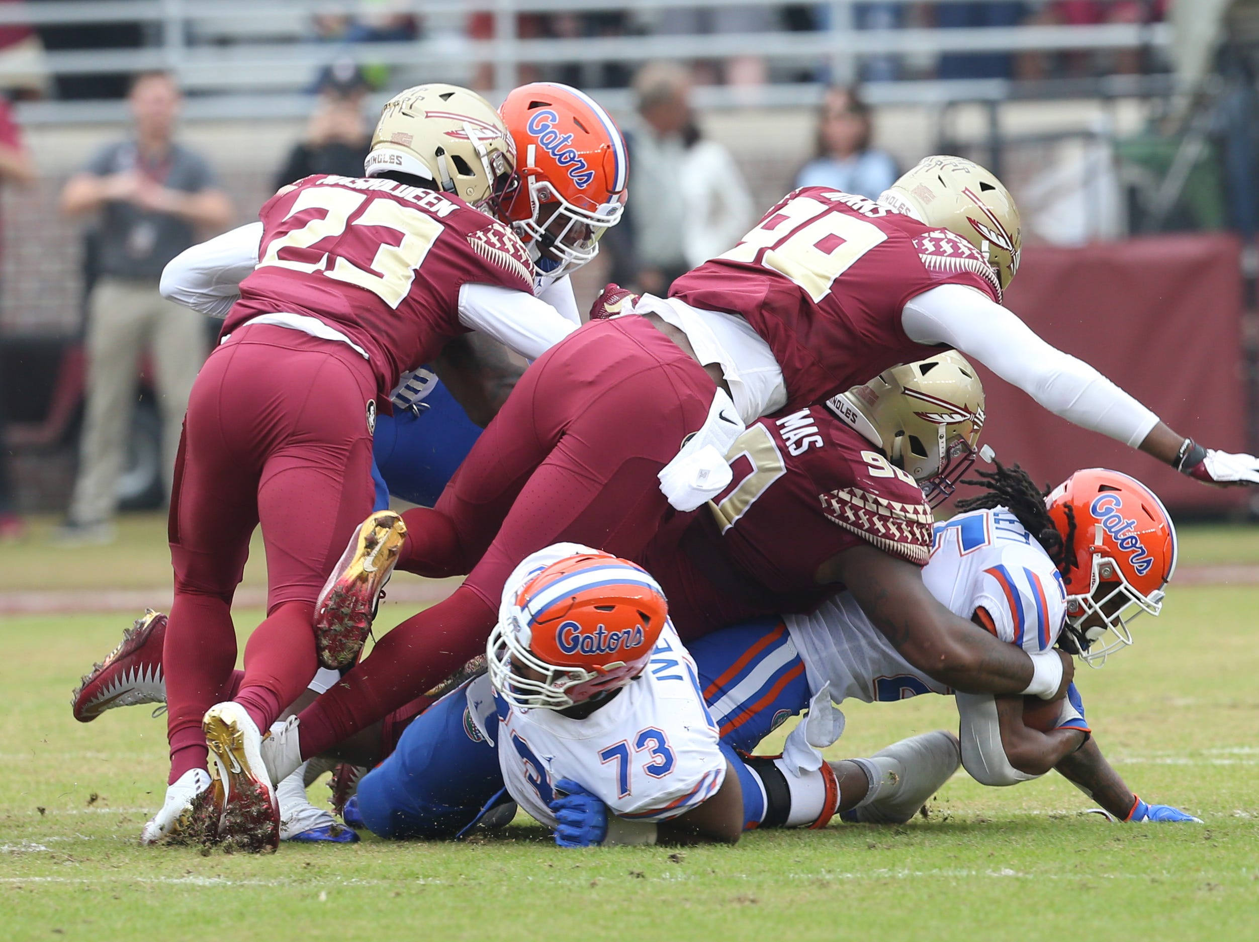 Florida Gators running back Jordan Scarlett (25) gets taken down by the defense as the Florida State Seminoles take on their rival the Florida Gators in college football at Doak S. Campbell Stadium, Saturday, Nov. 24, 2018.