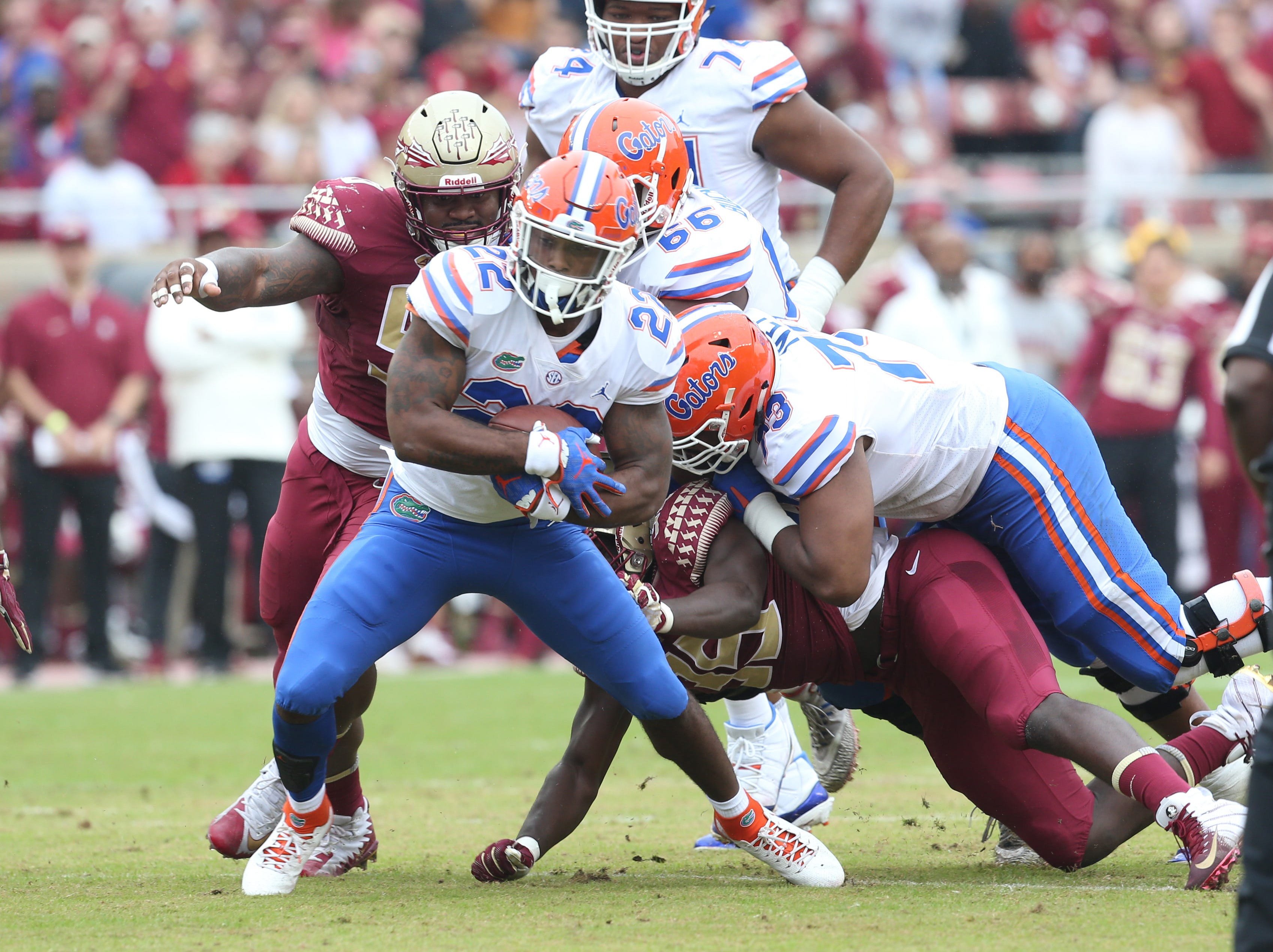 Florida Gators running back Lamical Perine (22) tries to fight off tackles from the defense as the Florida State Seminoles take on their rival the Florida Gators in college football at Doak S. Campbell Stadium, Saturday, Nov. 24, 2018.