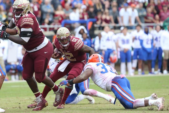 Florida State Seminoles quarterback Deondre Francois (12) weaves between defenders as the Florida State Seminoles take on their rival the Florida Gators in college football at Doak S. Campbell Stadium, Saturday, Nov. 24, 2018.