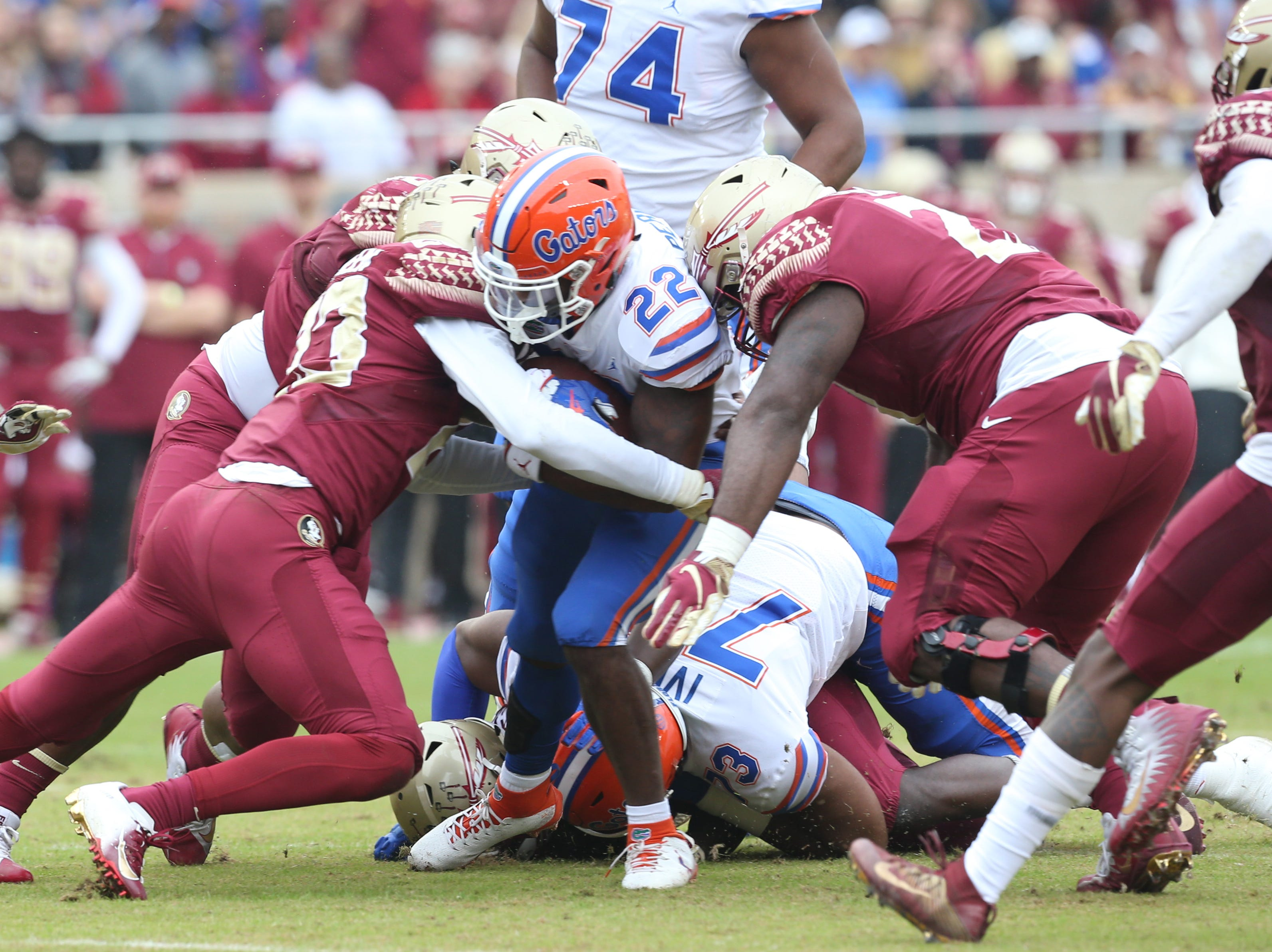 Florida Gators running back Lamical Perine (22) gets swarmed by the defense as the Florida State Seminoles take on their rival the Florida Gators in college football at Doak S. Campbell Stadium, Saturday, Nov. 24, 2018.